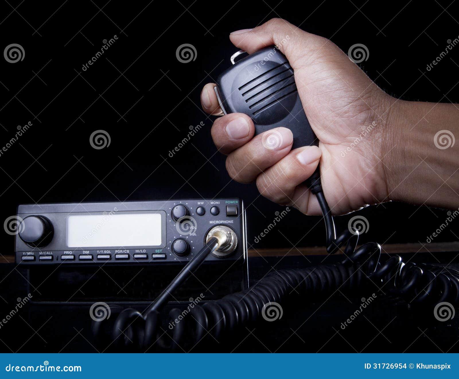Mão do orador e da imprensa guardarando de rádio amadores