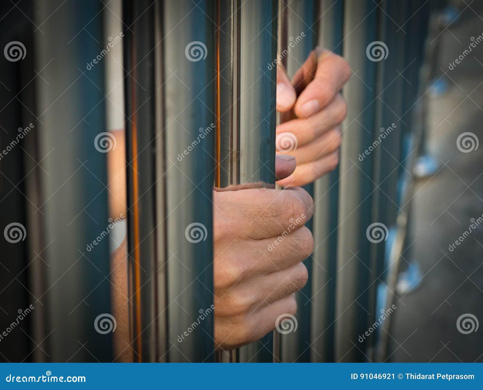 Mão do prisioneiro que guarda barras da prisão na cadeia