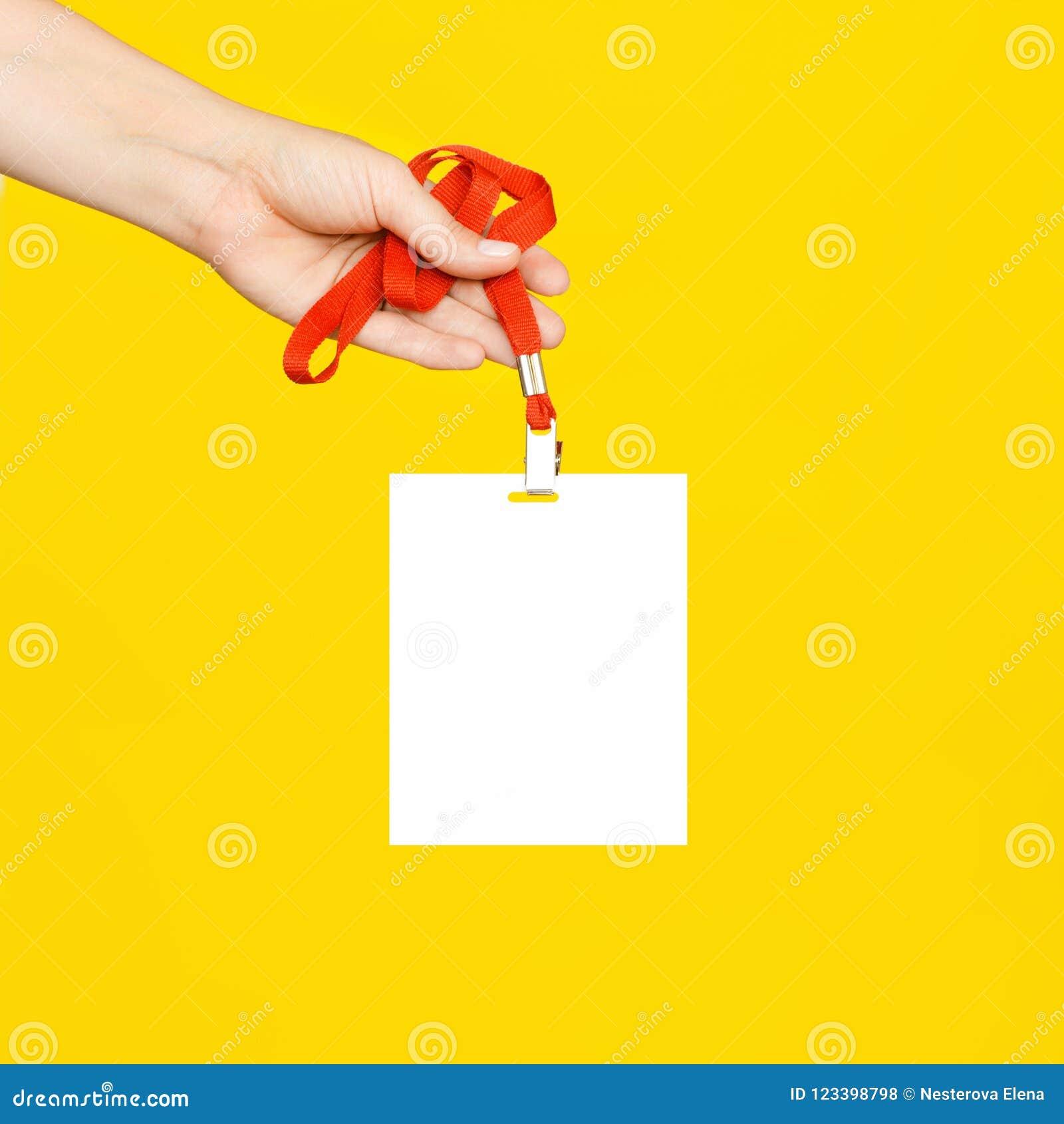 A mão do ` s da mulher guarda um crachá branco limpo em um cabo vermelho no fundo amarelo