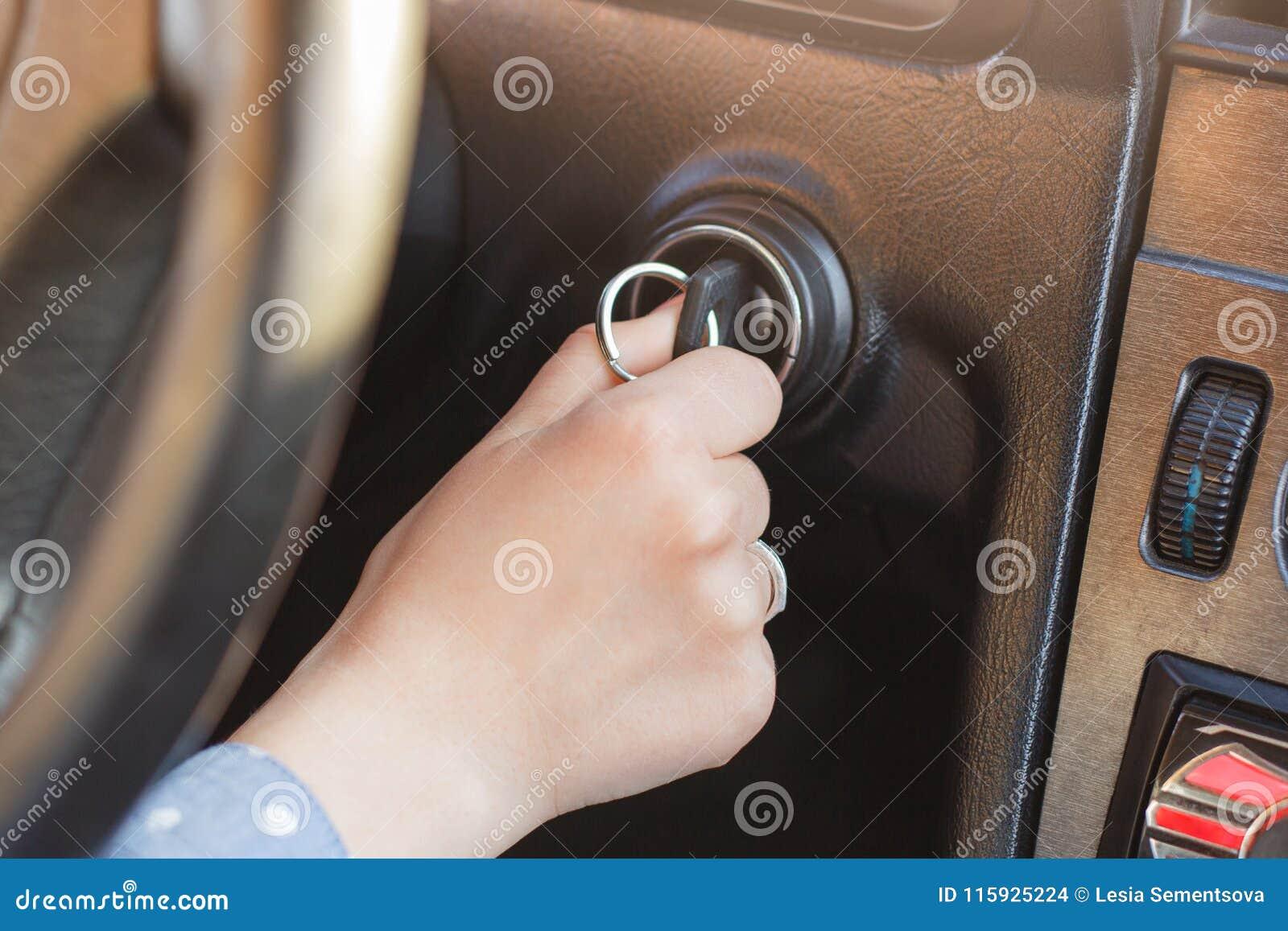 A mão do ` s da mulher na chave do ` s do carro, tentativas para ligar o motor, gerencie sobre a chave no buraco da fechadura, au