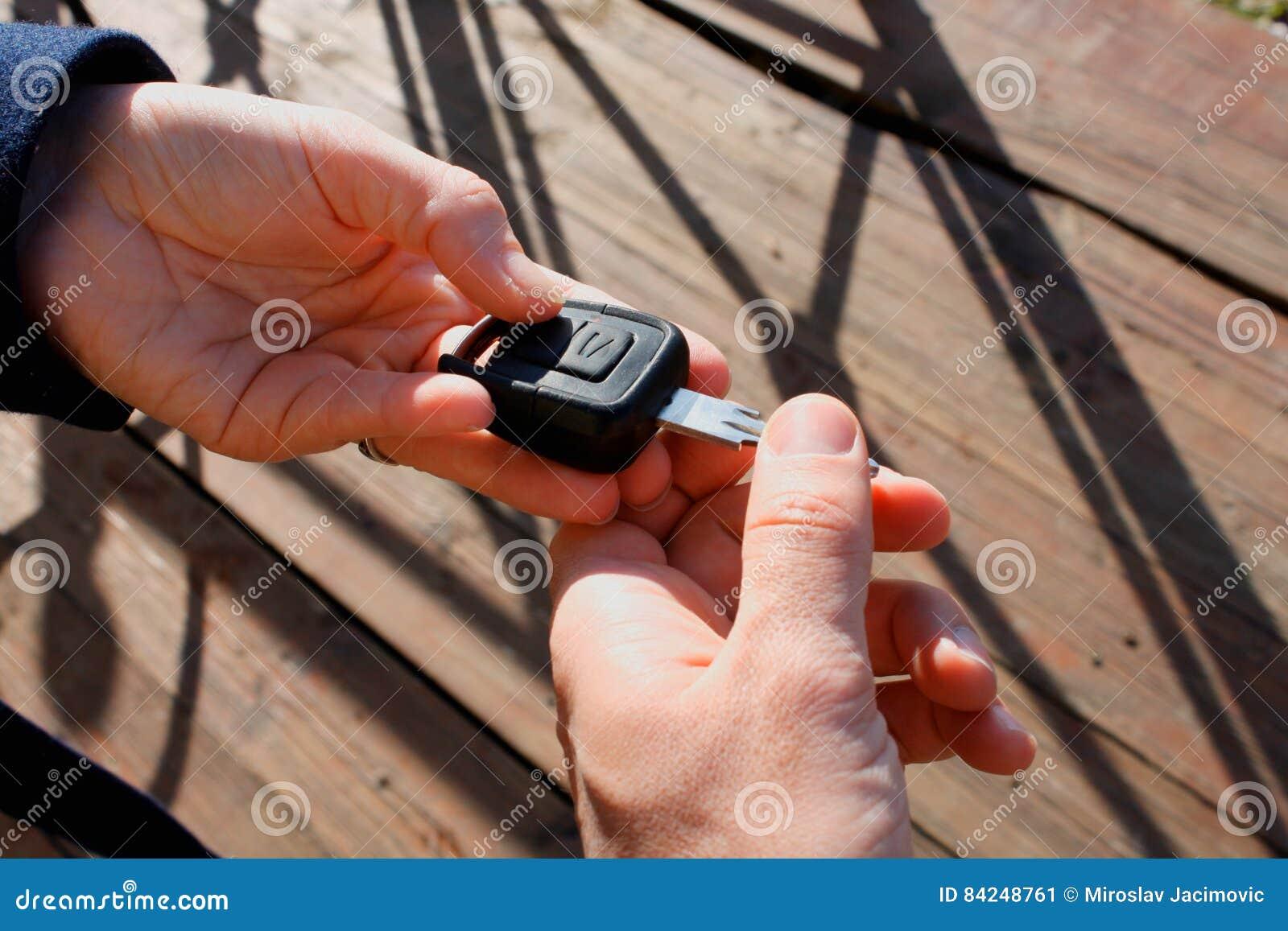 Mão do ` s do comprador que toma uma chave do carro