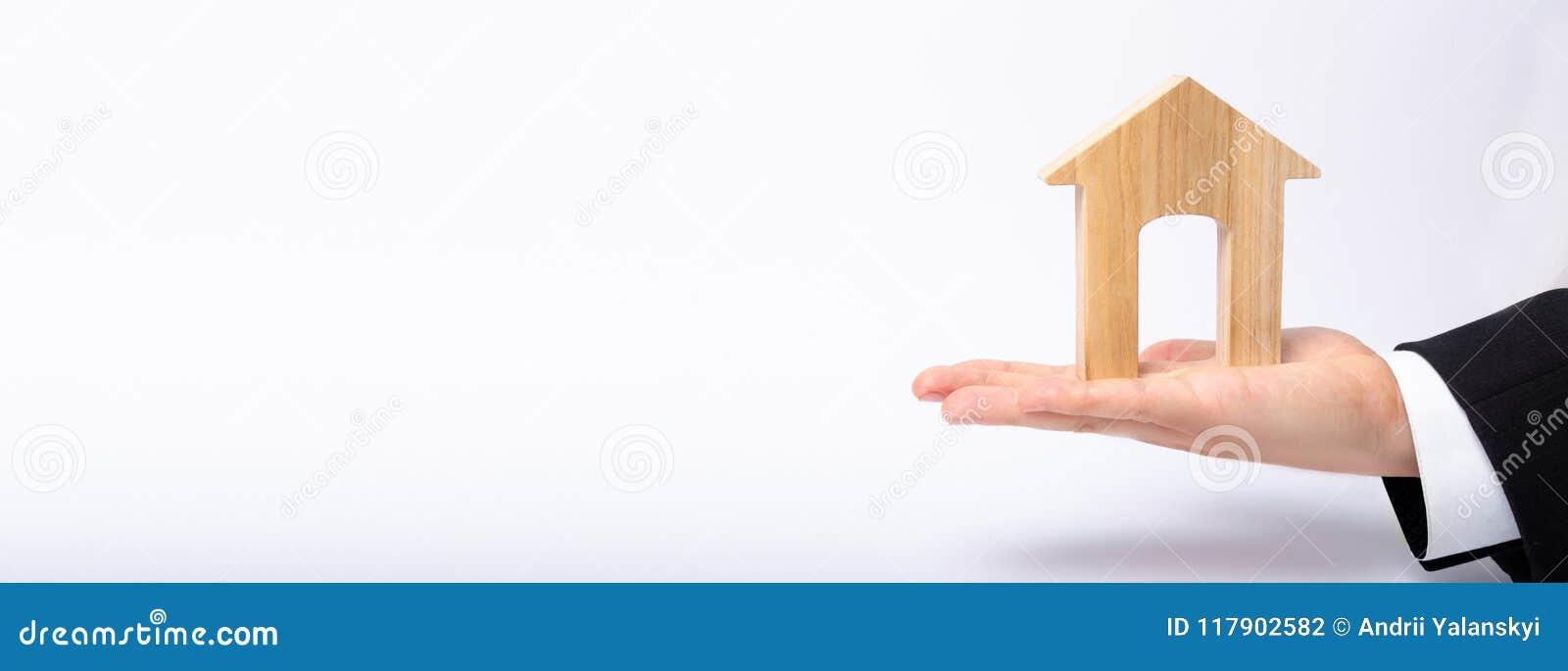 A mão do ` s do homem de negócios estica uma casa de madeira com uma grande entrada O conceito dos imóveis comerciais