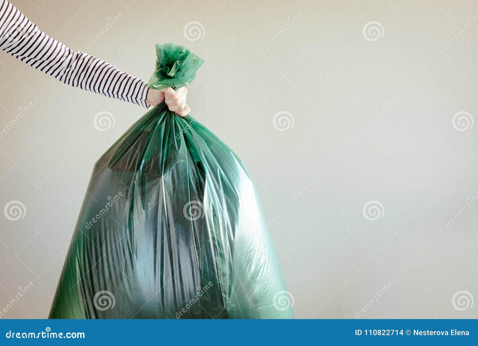 Mão do ` s do homem que guarda o saco de lixo
