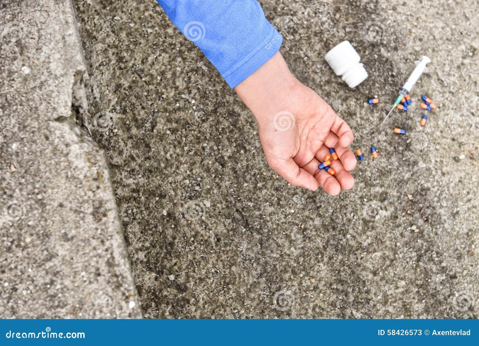 Mão do viciado em drogas perto de uma seringa e dos comprimidos Simule um suici