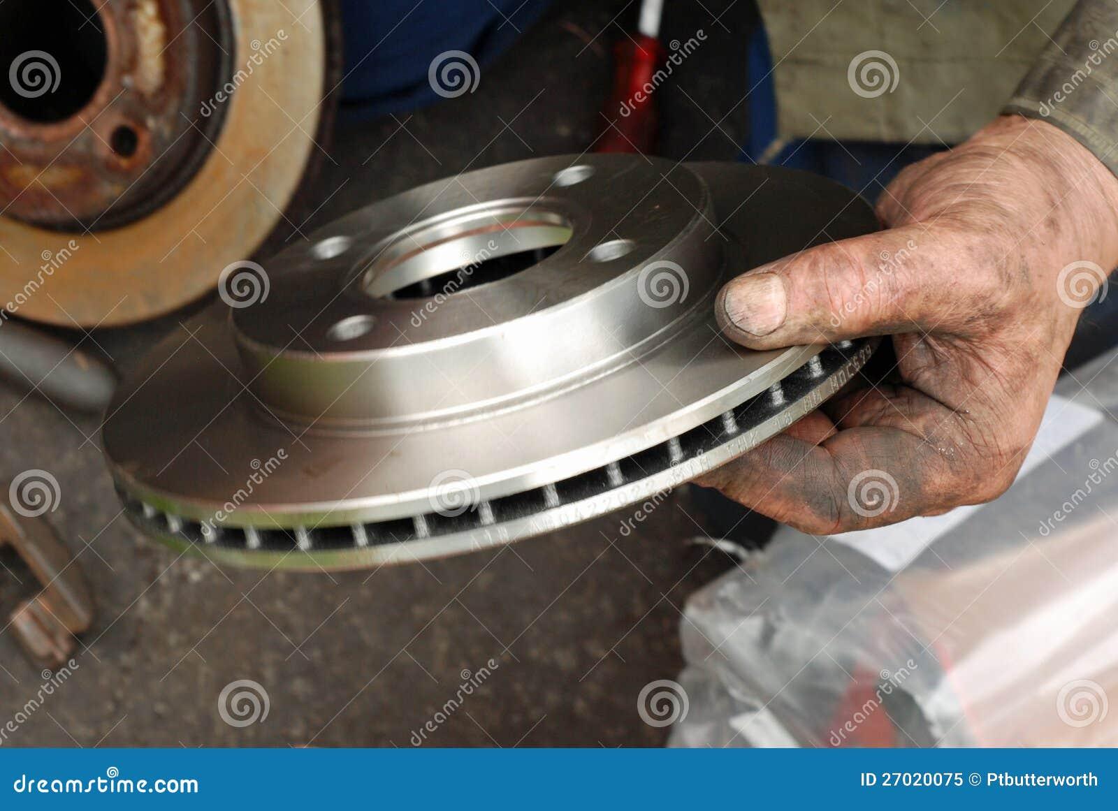 Mão dos mecânicos que cabe o freio de disco novo.