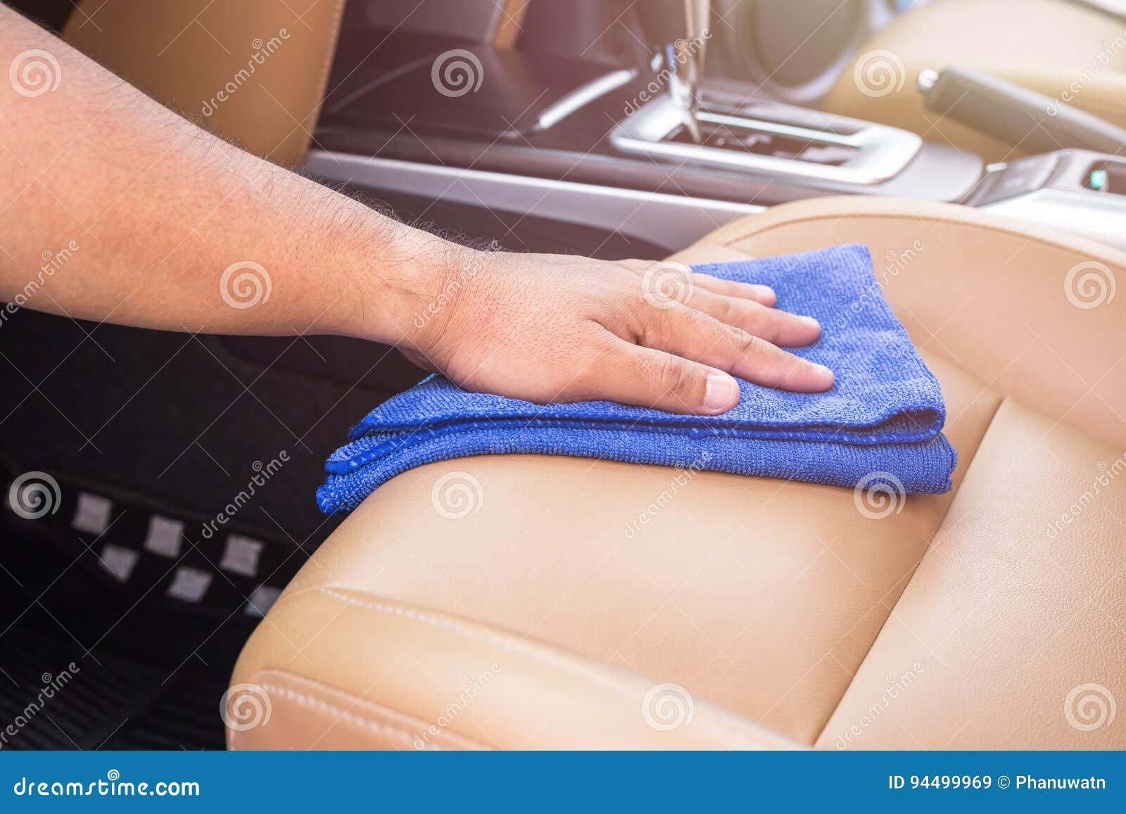 Mão dos povos que guardam o pano azul do microfiber e que limpam para dentro