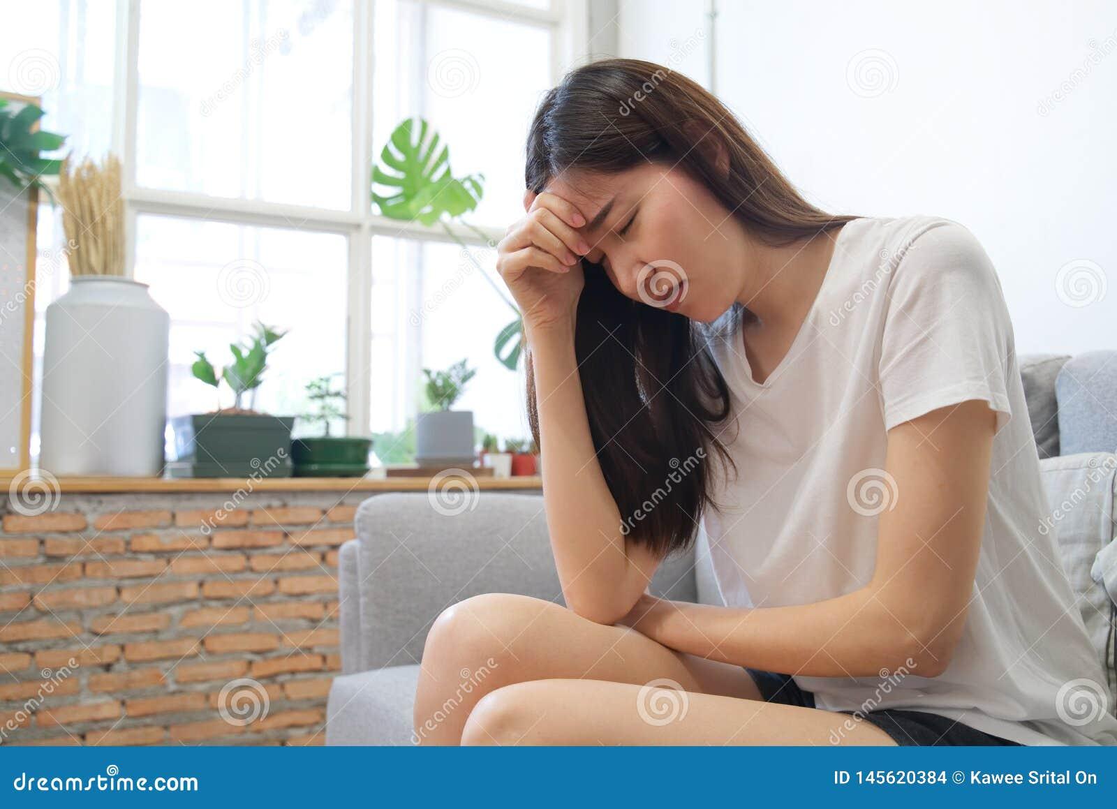 Mão em templos da menina asiática da tristeza infeliz nova que senta-se no sofá Está sentindo não muito bom devido a sua doença e