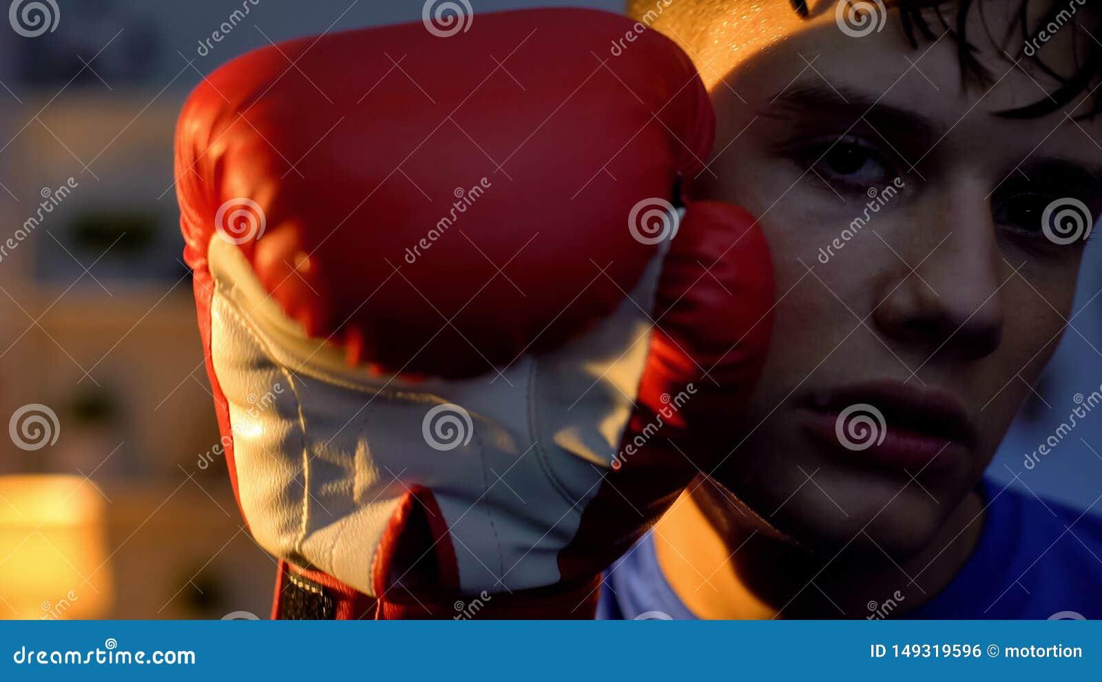 M?o esgotada da terra arrendada do adolescente na luva de encaixotamento perto da cara que olha na c?mera