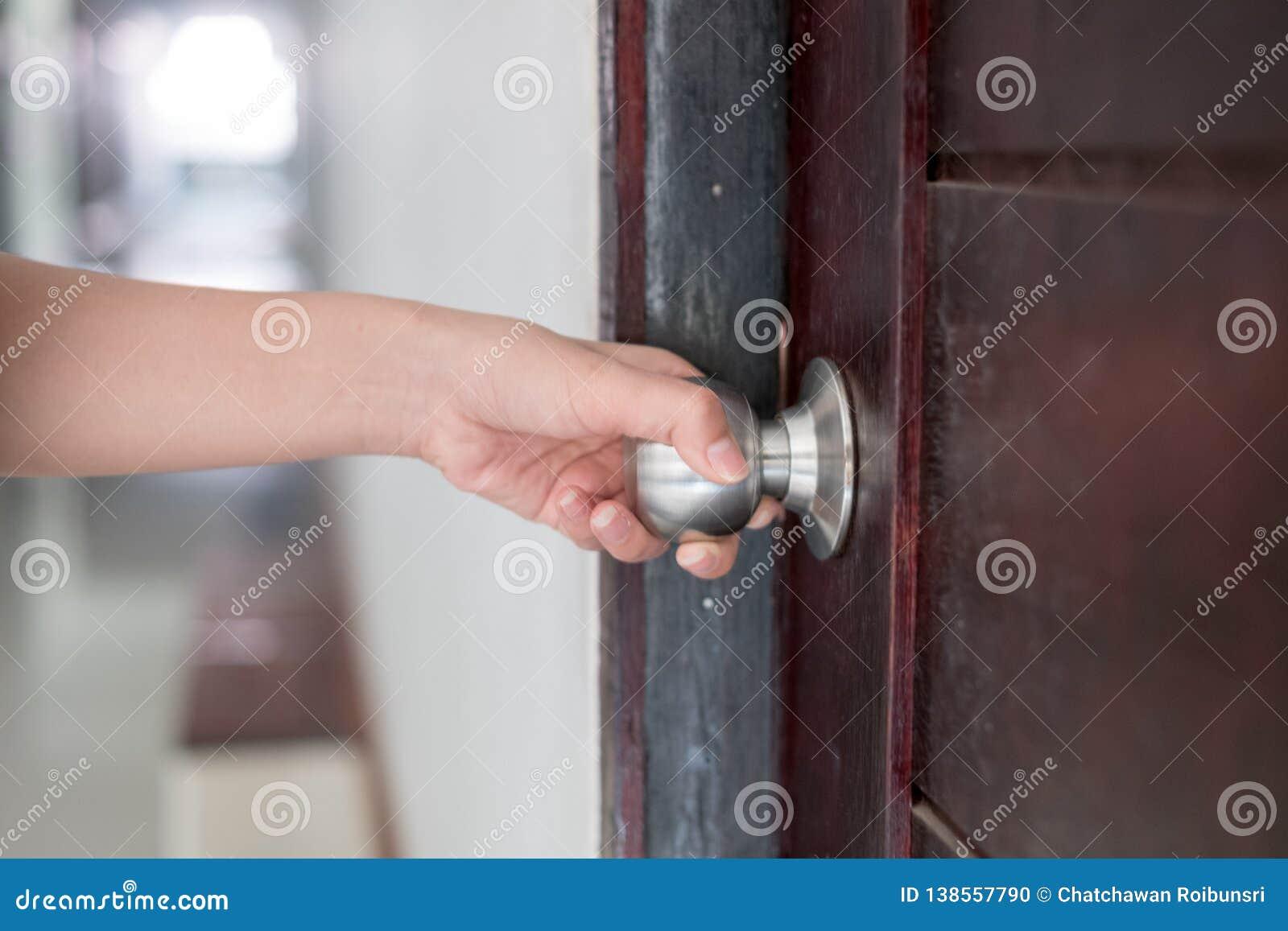 A mão está abrindo o botão de porta