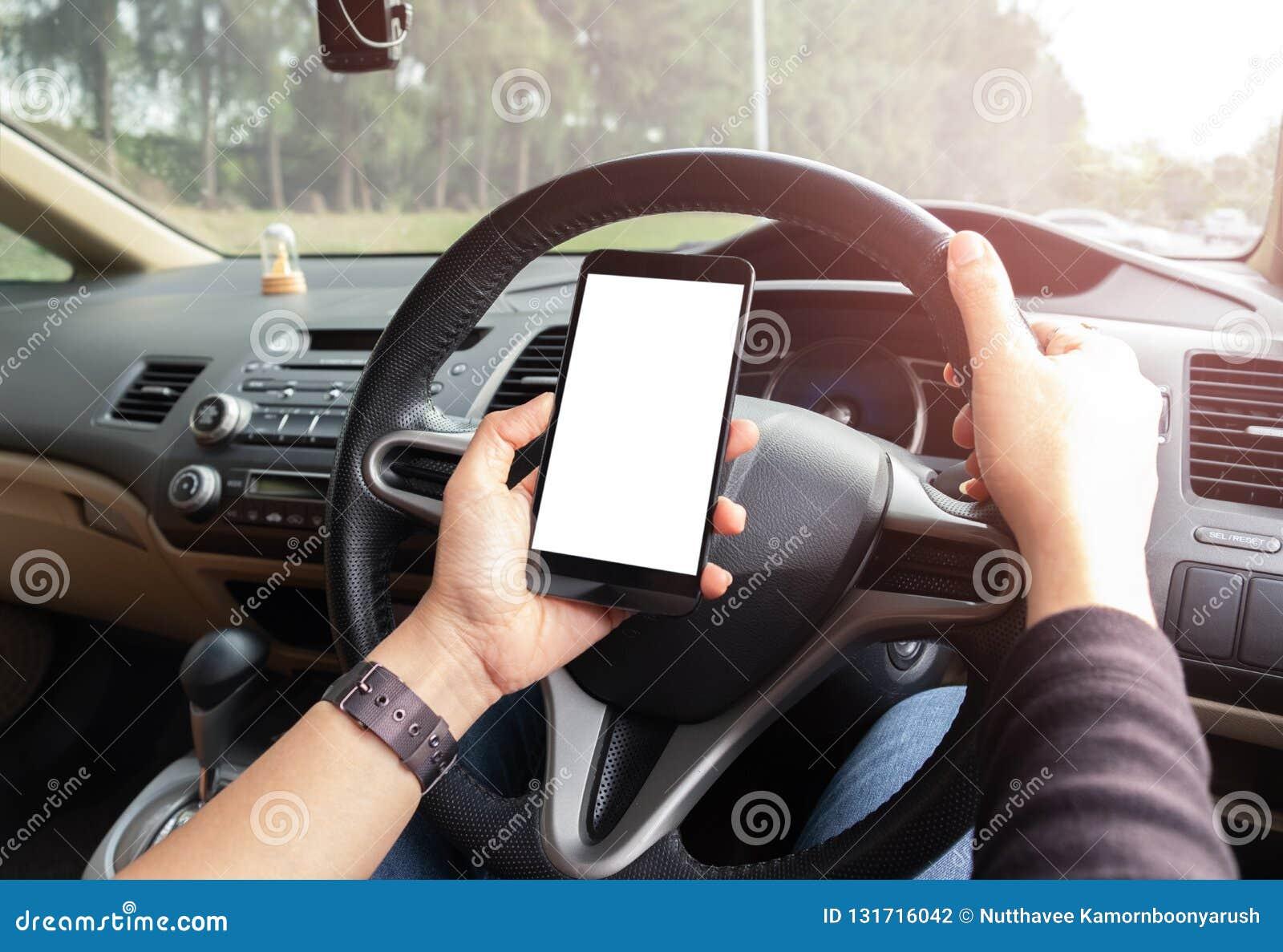 A mão está guardando um telefone do toque com a tela isolada no carro