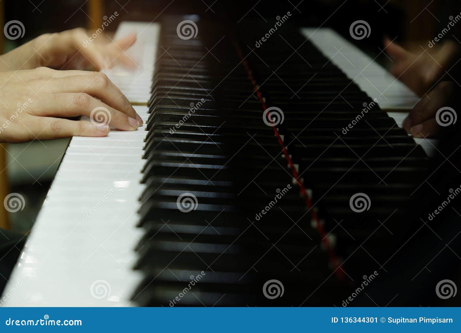 Mão fêmea do close-up que joga o piano de cauda