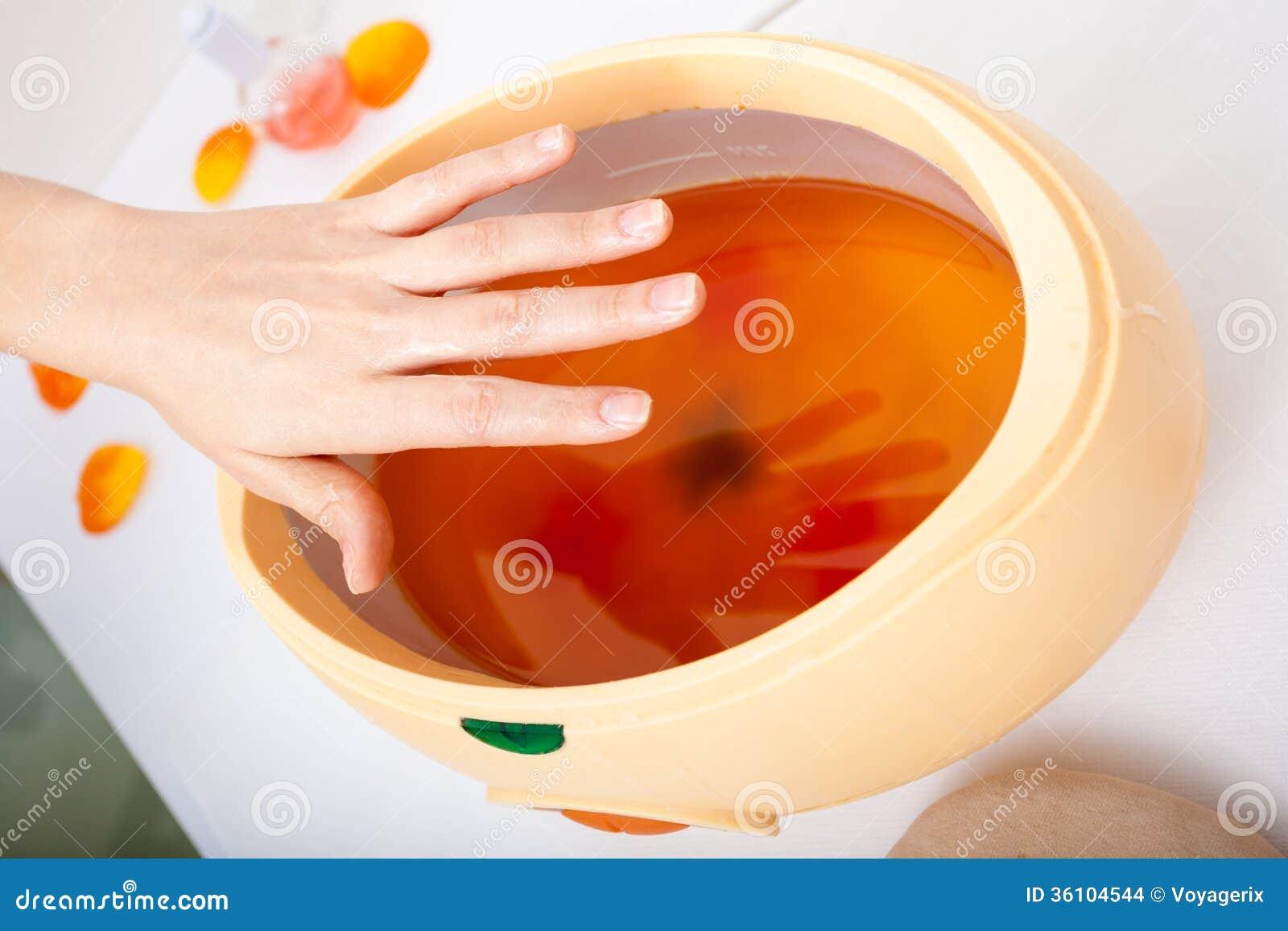Mão fêmea e bacia alaranjada da cera de parafina. Mulher no salão de beleza