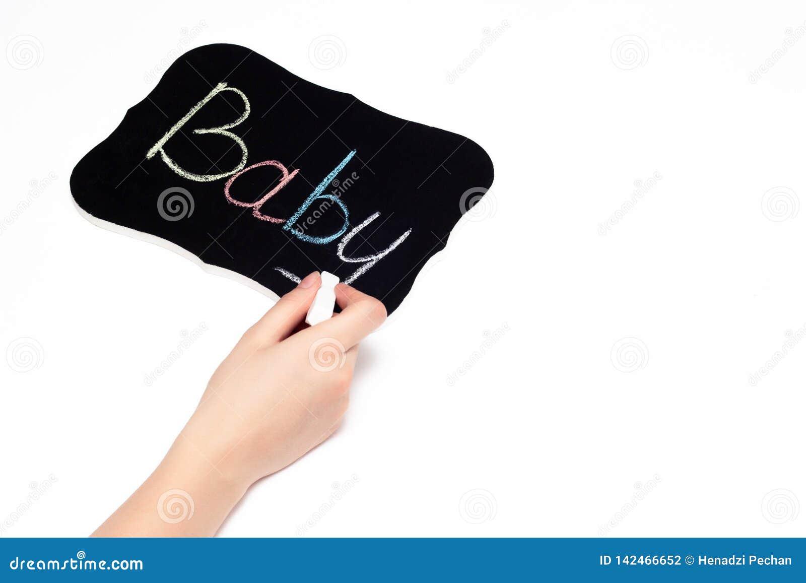 A mão fêmea escreve no giz em uma tabuleta a criança da palavra, o conceito da adoção e sonhos de uma criança, infertilidade, clo