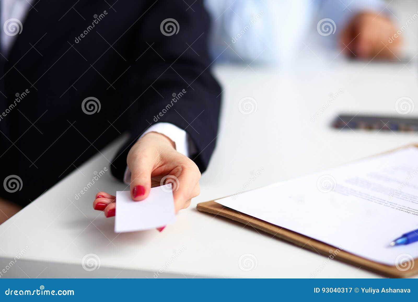 Mão fêmea que guarda um cartão vazio que senta-se na mesa, foco seletivo