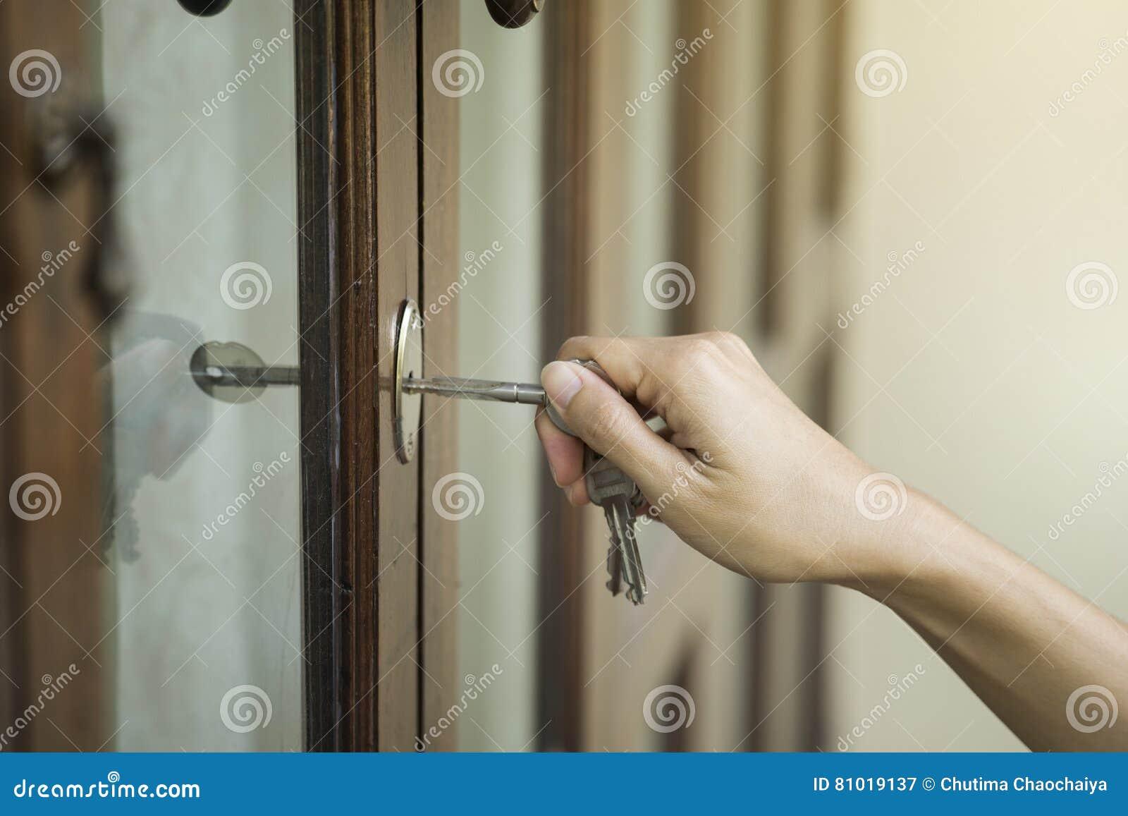 Mão fêmea que põe a chave da casa no fechamento de porta da rua da casa