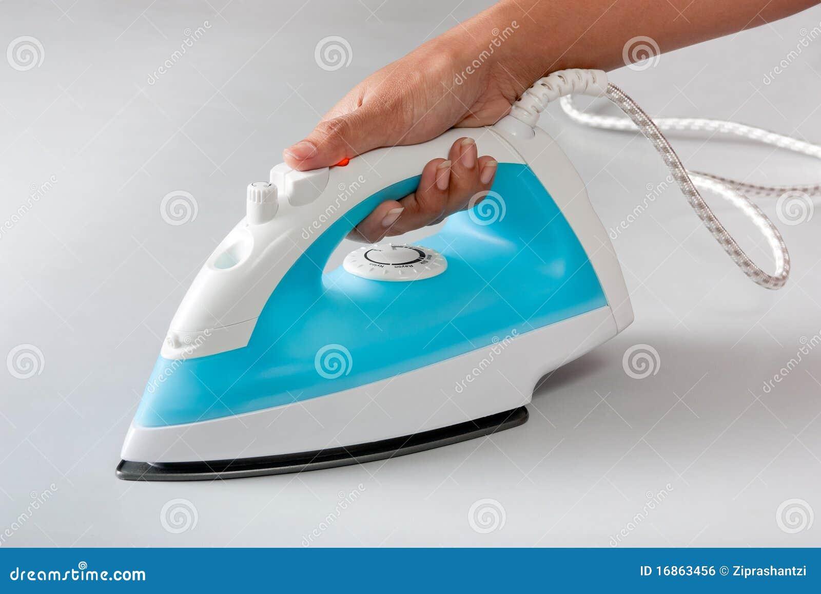 Mão fêmea que prende o ferro de vapor elétrico