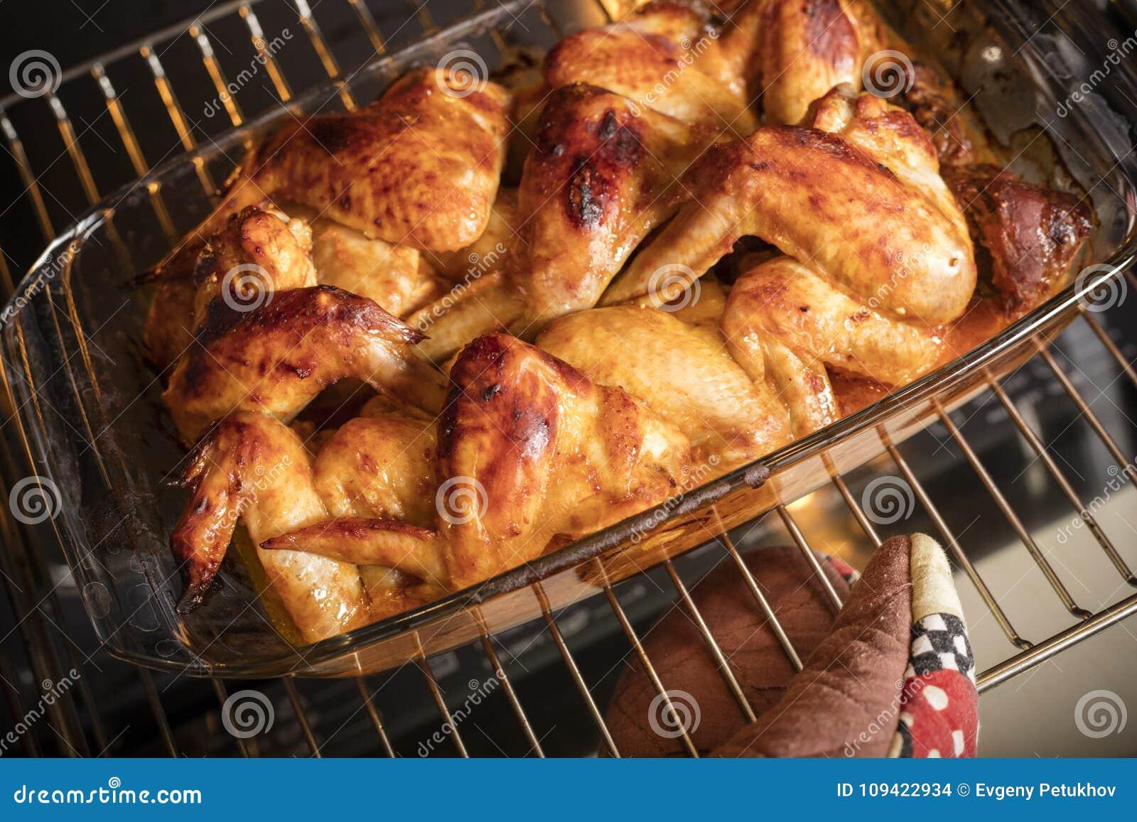 A mão fêmea retira as asas de galinha do forno