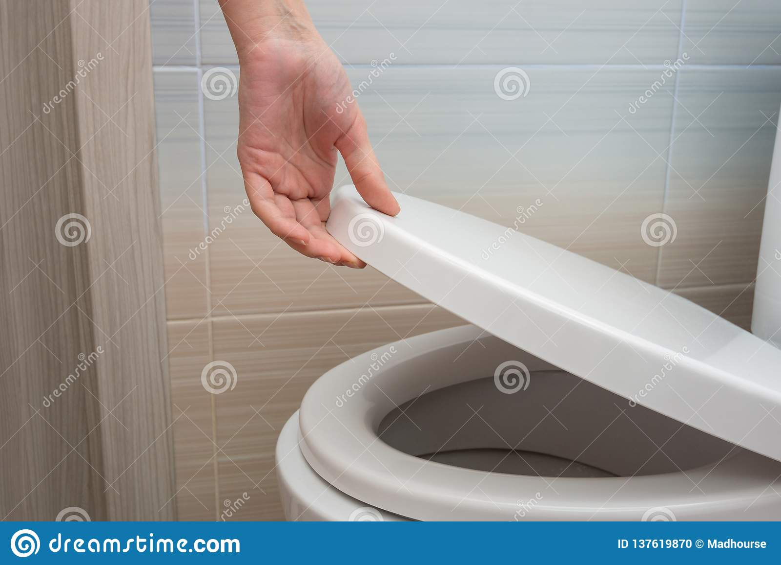 A mão fecha ou abre a tampa do toalete