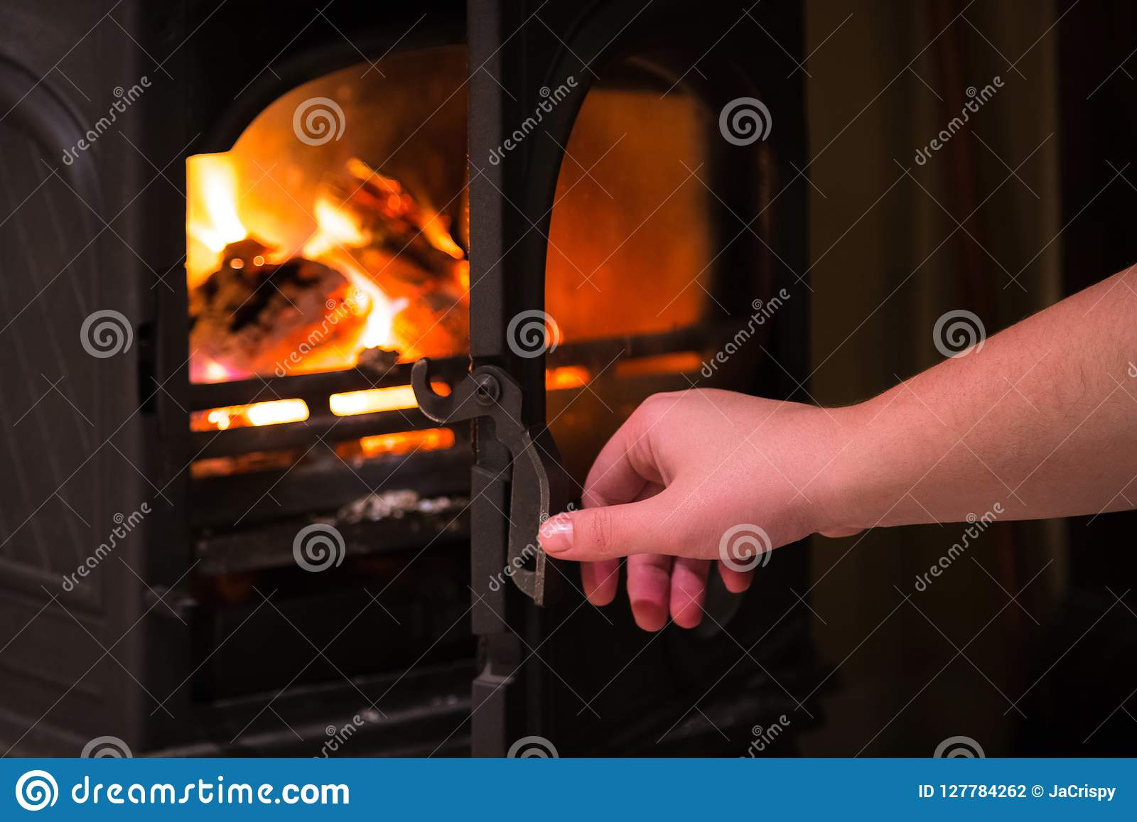 Mão humana que abre uma porta da chaminé ardente com l de madeira