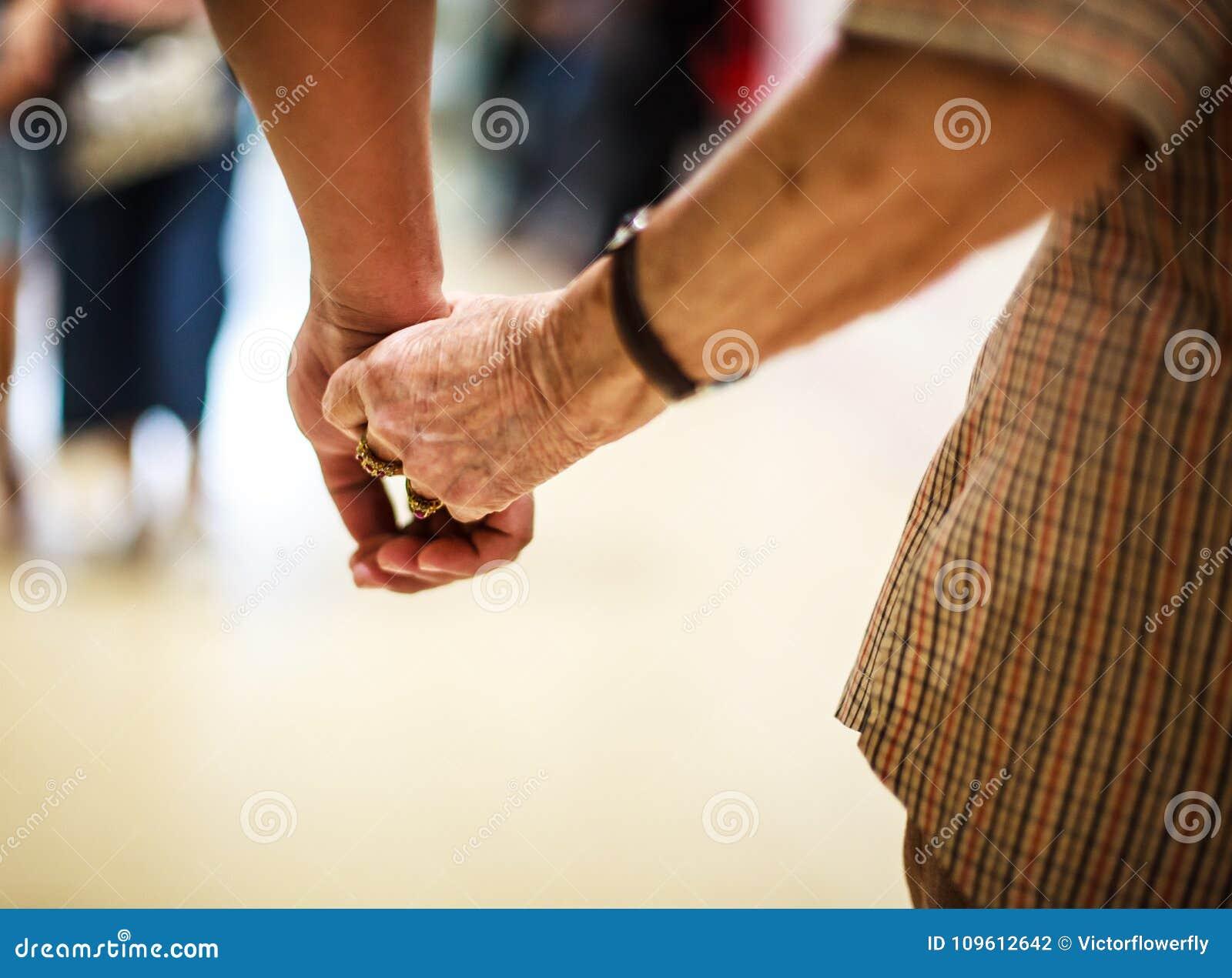 Mão idosa enrugada do ` s da mulher que guarda à mão do ` s do homem novo, andando no shopping Relação de família, saúde, ajuda,