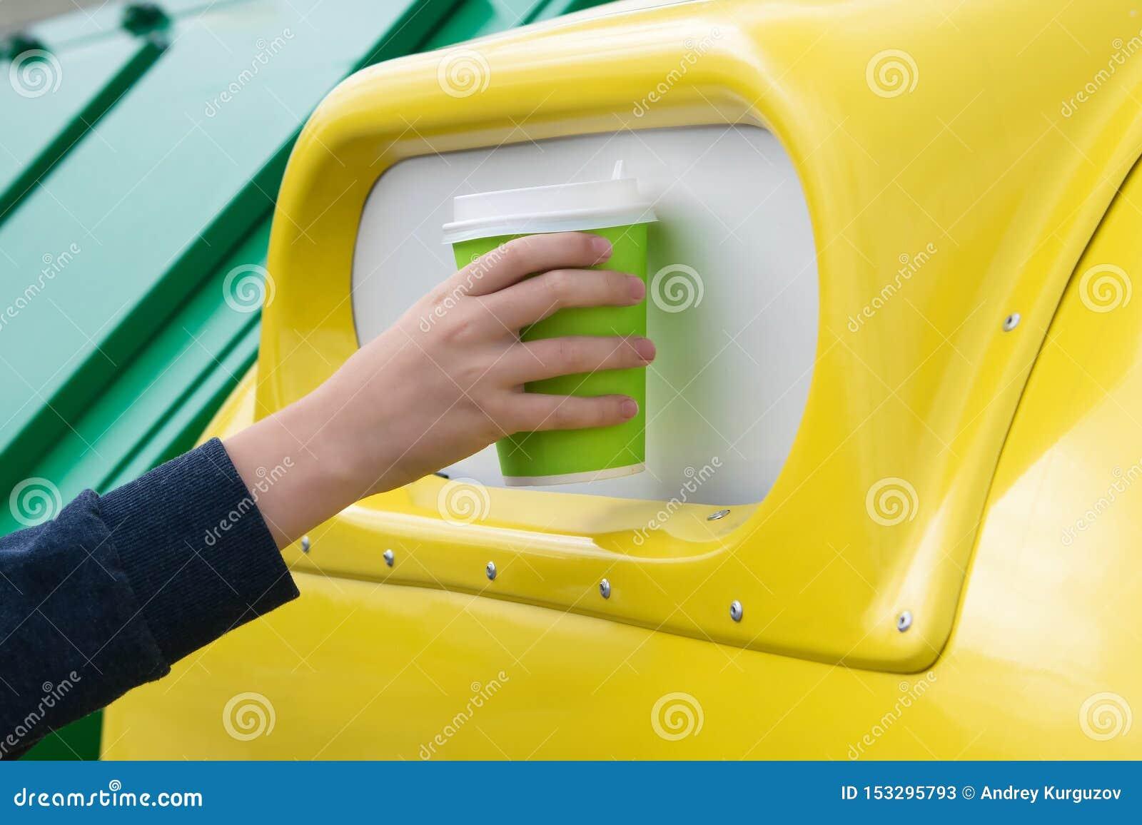 A mão joga o copo de papel em um tanque amarelo do lixo, close-up