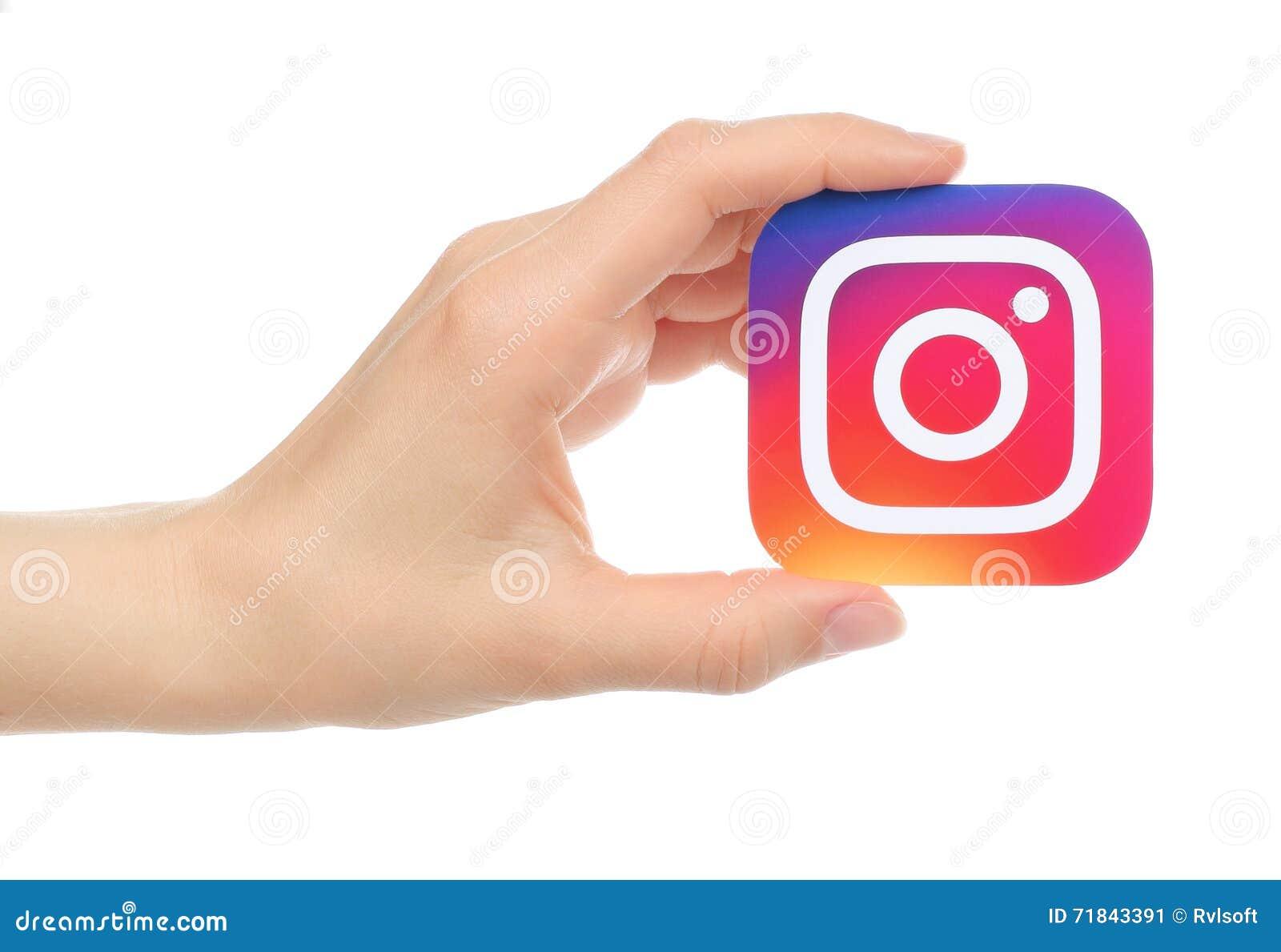 A mão mantém o logotipo novo de Instagram impresso no papel