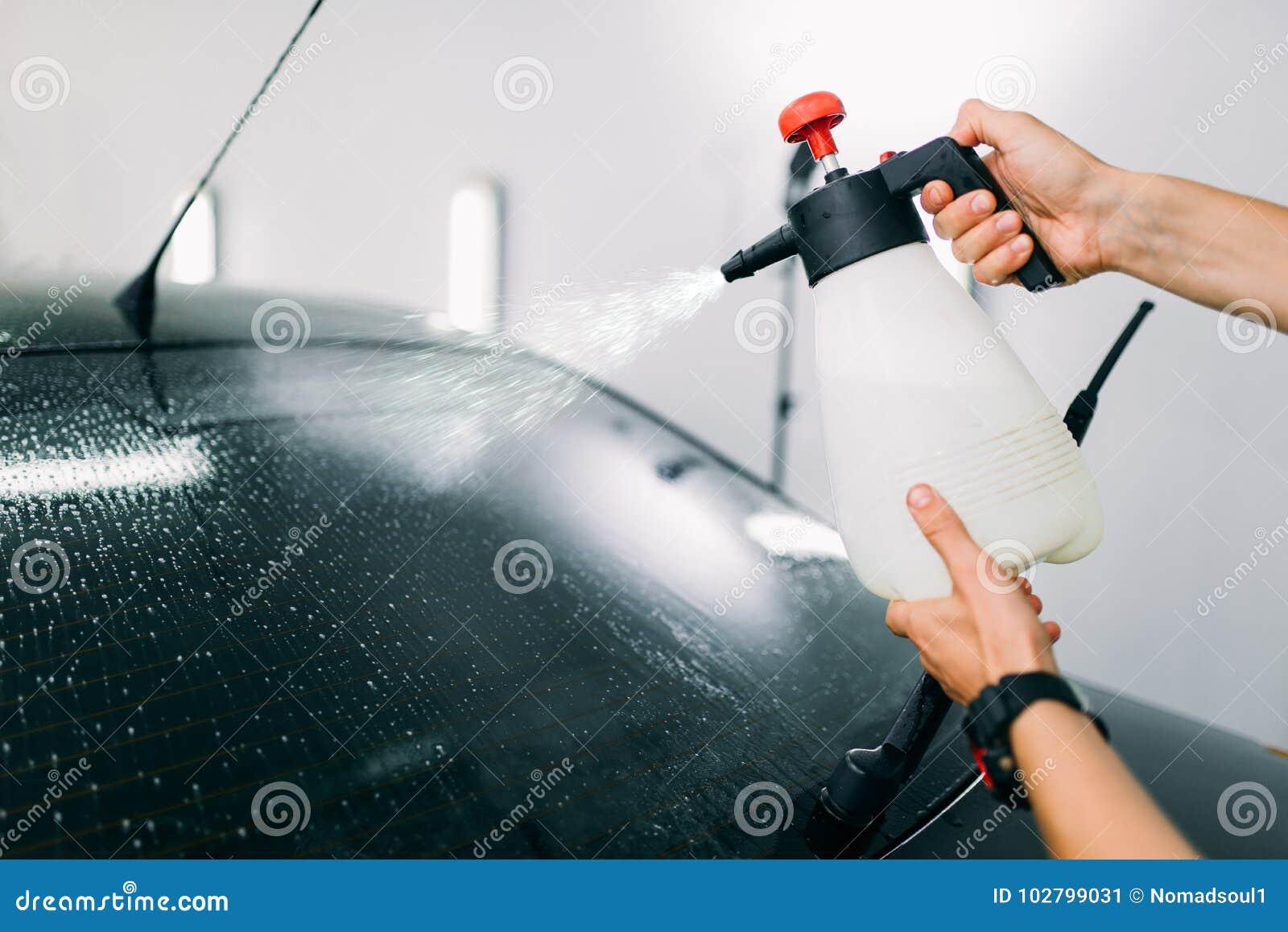 Mão masculina com pulverizador, a instalação do matiz da janela de carro