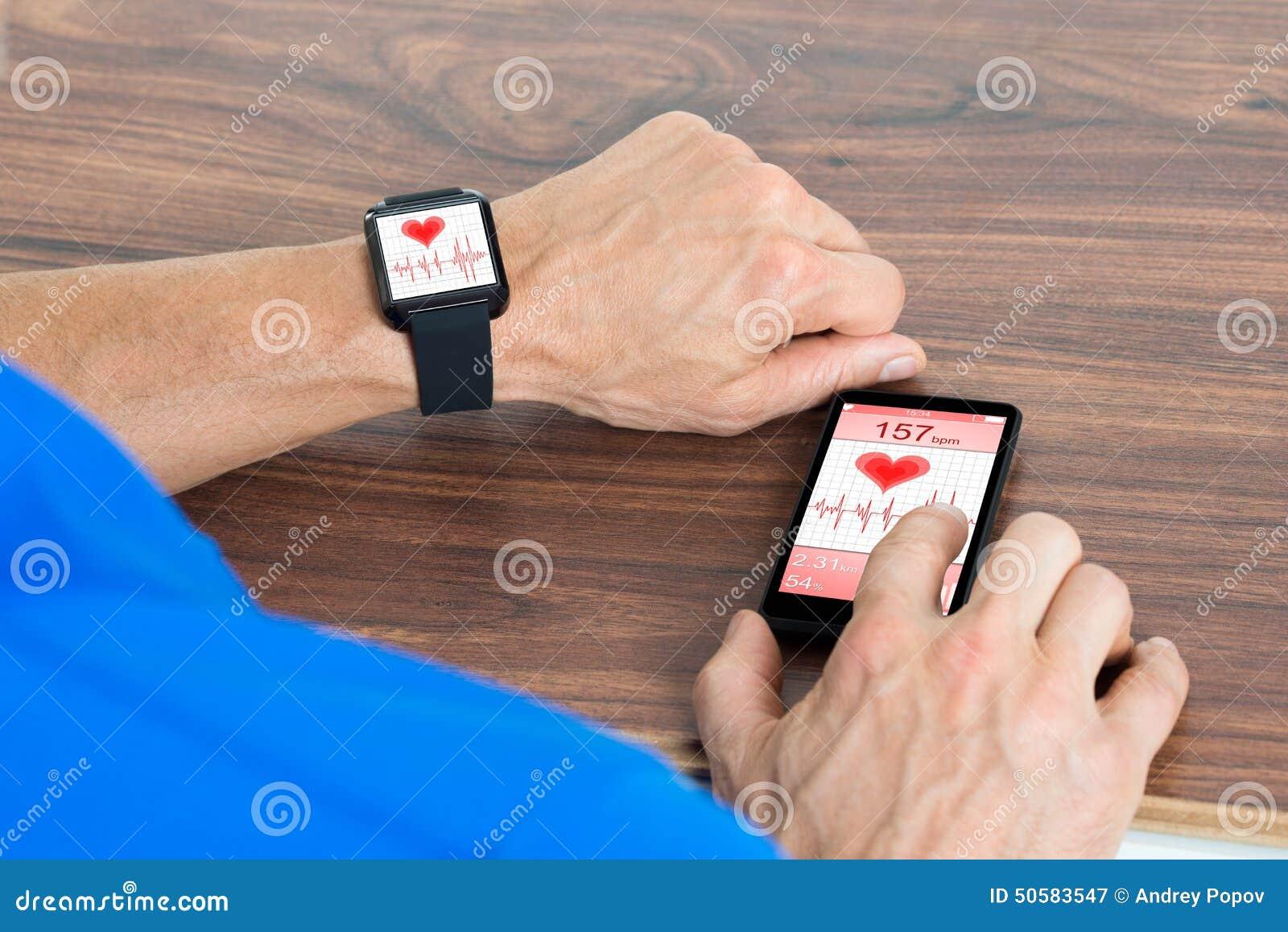 Mão masculina com smartwatch e telefone celular