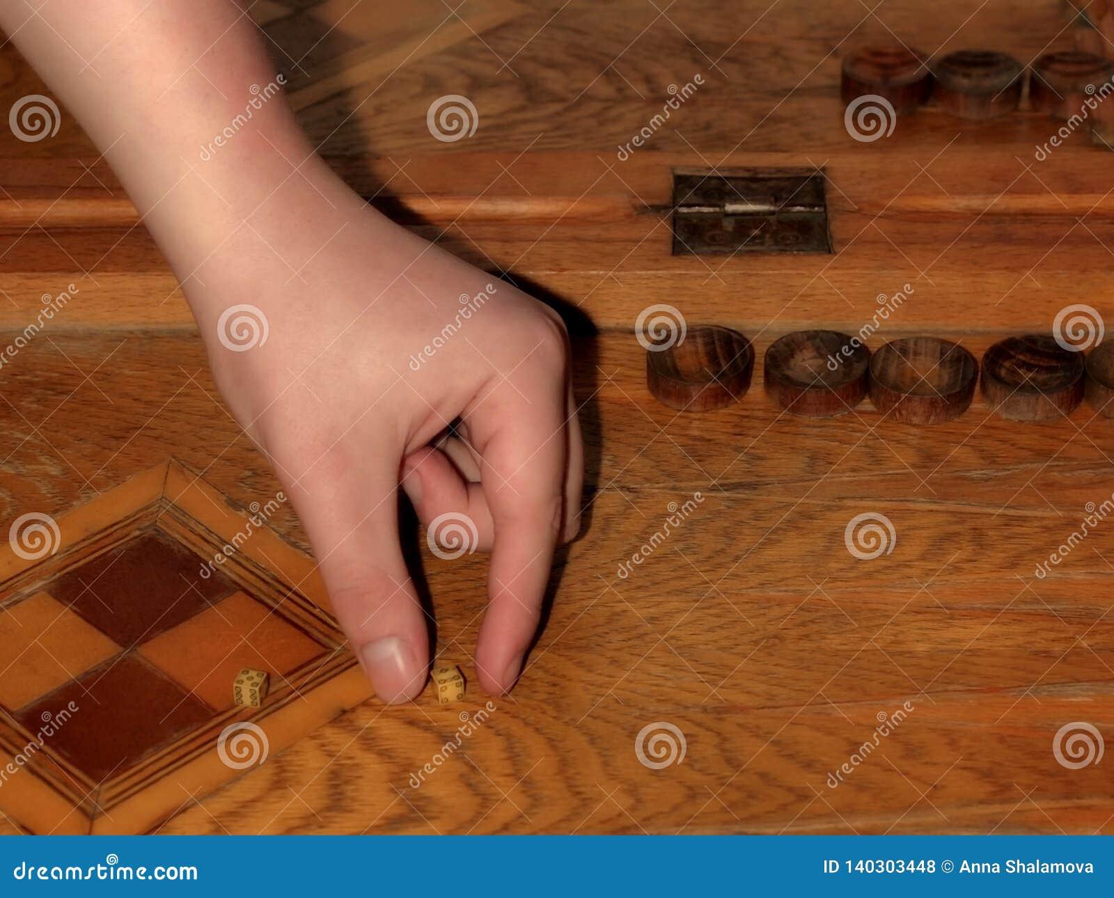 A mão masculina guarda dados no jogo da gamão