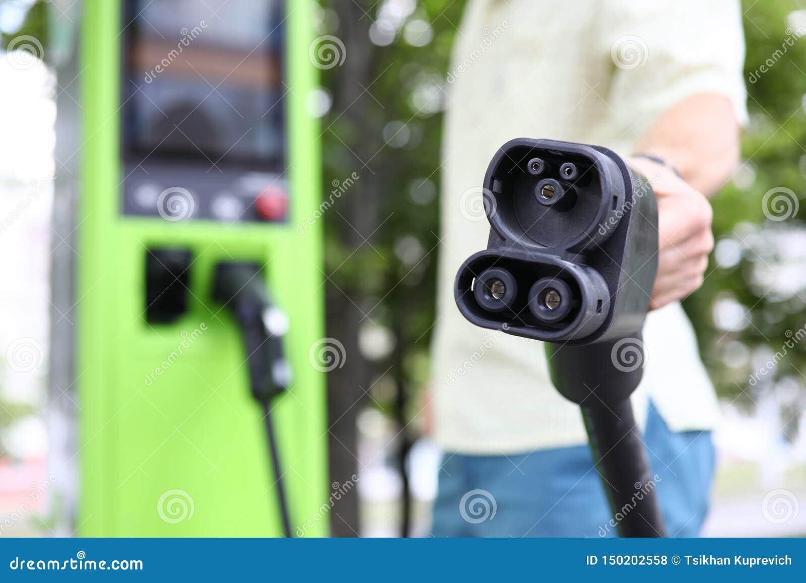 Mão masculina que guarda o cabo de carregamento do carro do carro preto