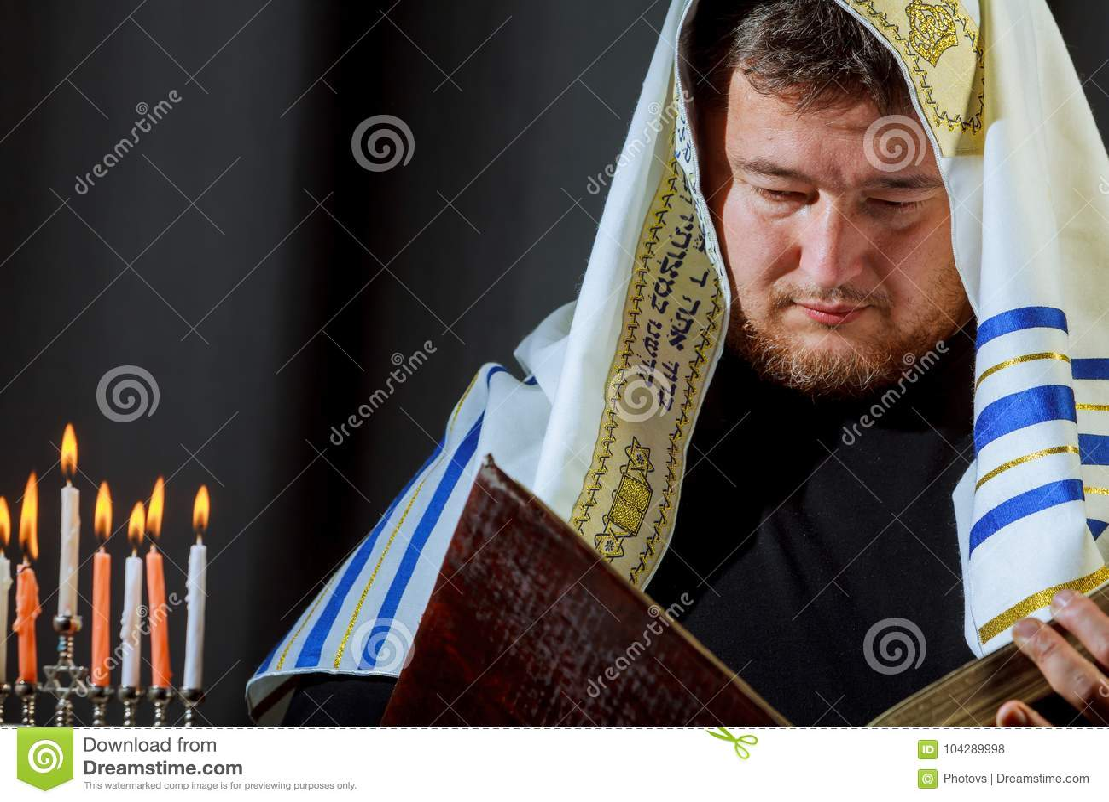 Mão masculina que leve velas no menorah no Hanukkah da tabela