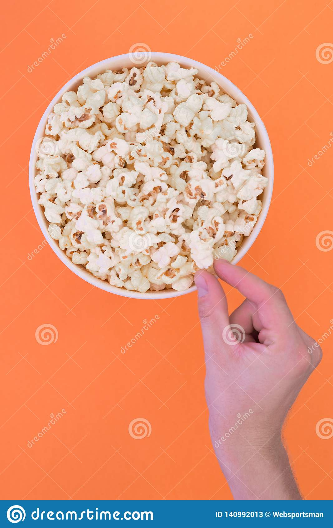 A mão masculina toma uma pipoca de um copo de papel em um fundo alaranjado O homem come a pipoca