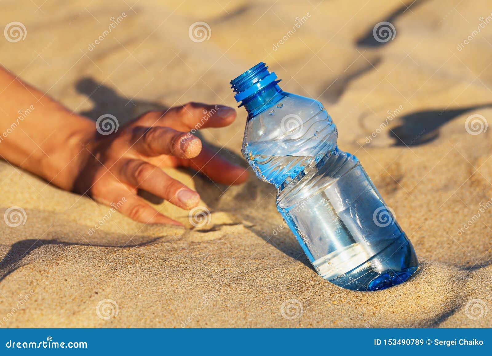 A mão na areia alcança para uma garrafa da água potável Conceito da sede