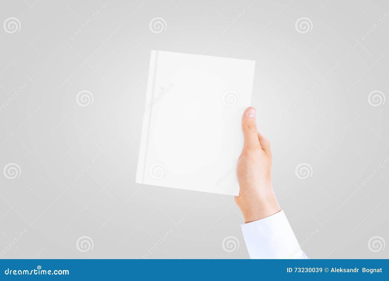 Mão na luva branca da camisa que guarda o livro vazio fechado