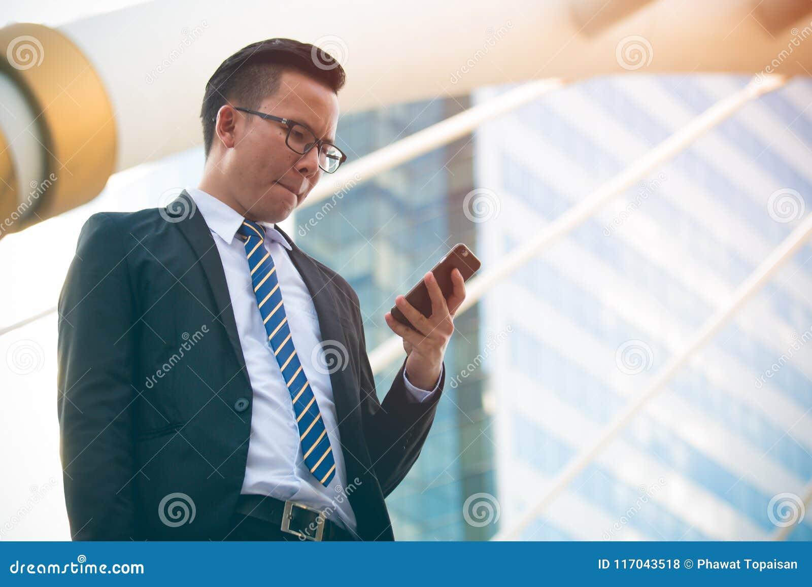 Mão nova moderna do terno do preto do desgaste do homem de negócios que guarda o smartphone Escritório exterior ereto profissiona