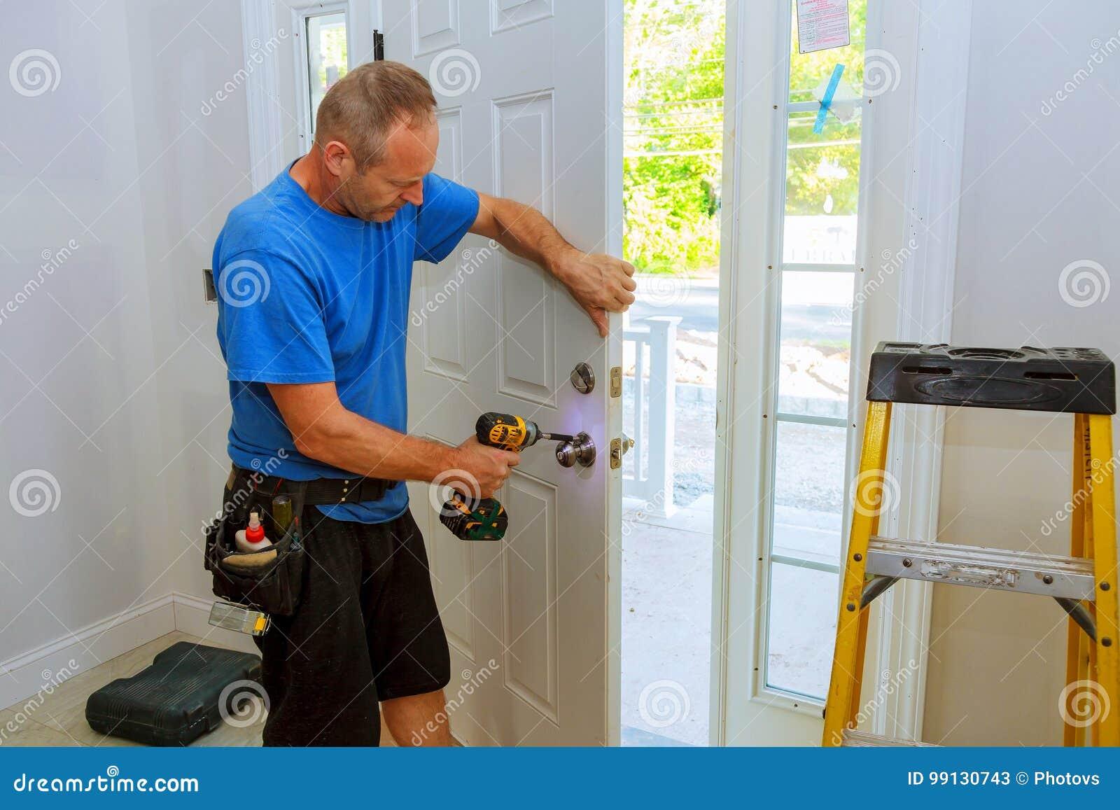 Mão & x27; o homem de s com chave de fenda instala o botão de porta
