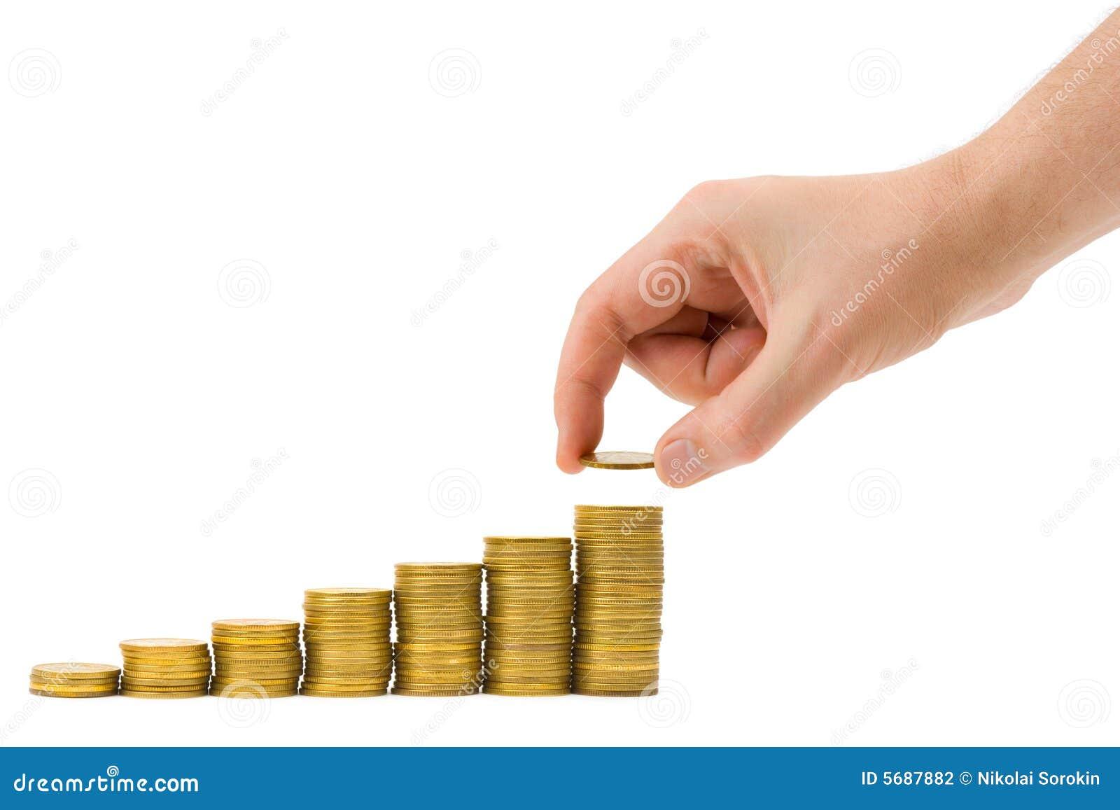 A mão põr a moeda à escadaria do dinheiro