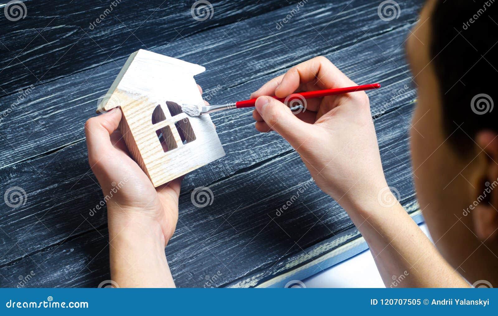 A mão pinta uma casa Conceito do reparo, passatempo, trabalho reparo