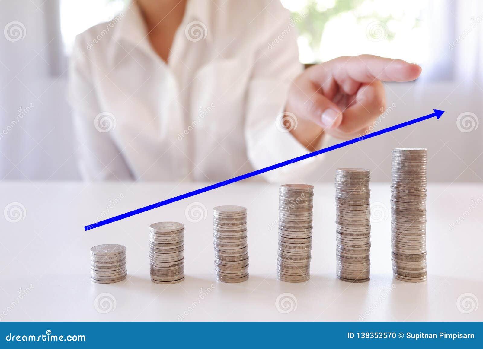 Mão que aponta a pilha crescente do dinheiro de aumento das moedas