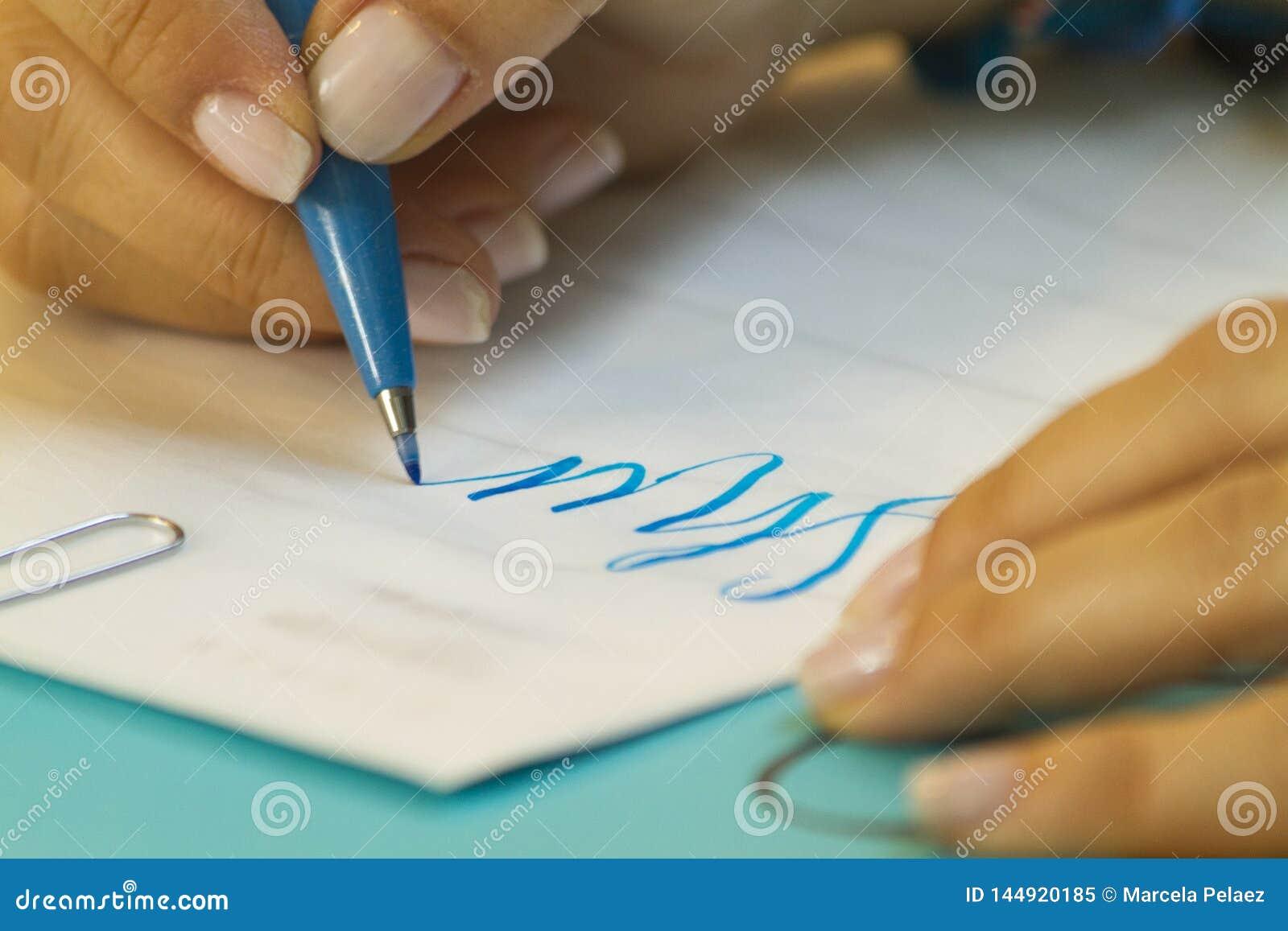 Mão que aprende a rotulação na classe com pena azul e Livro Branco