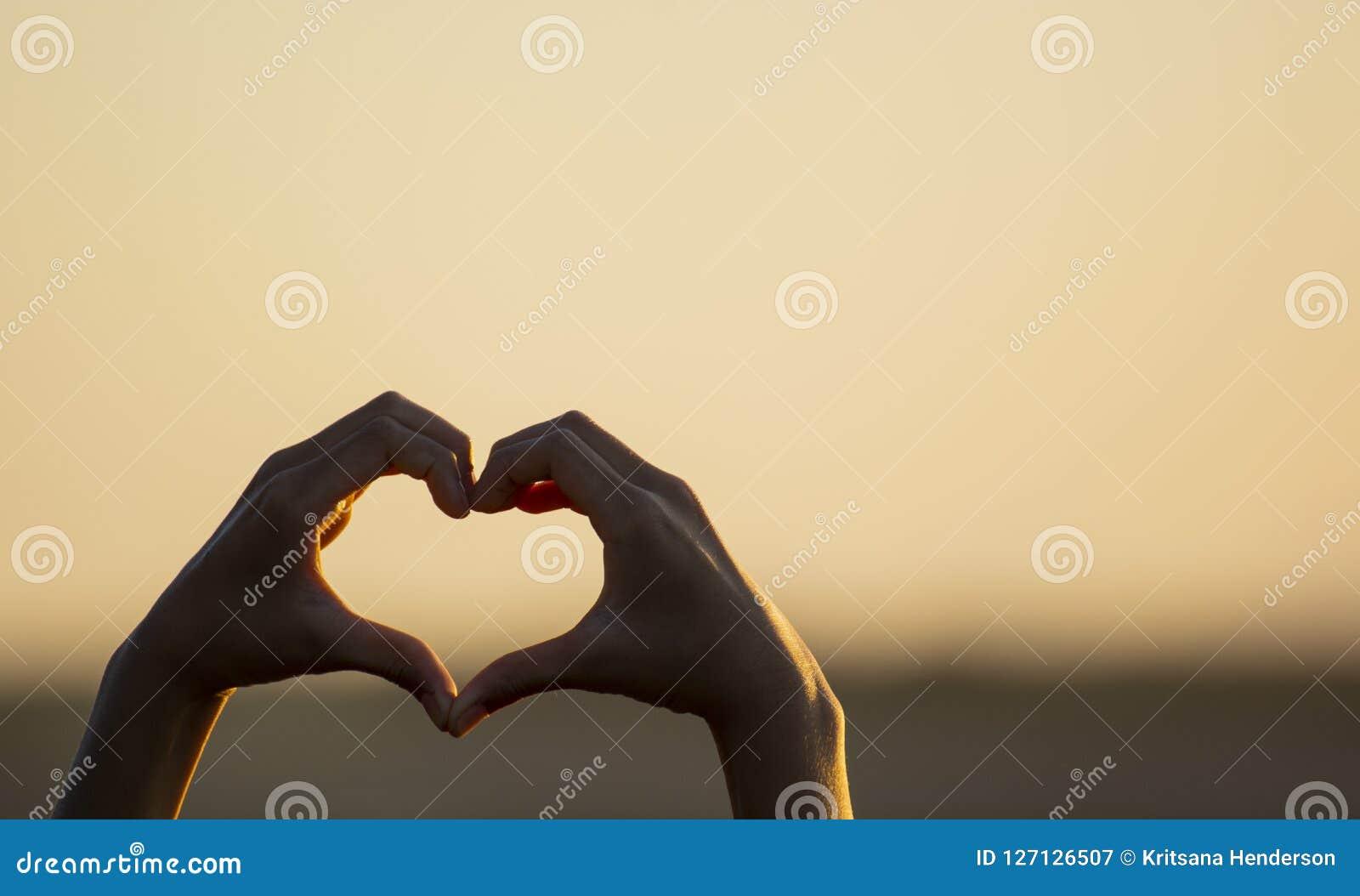 Mão que faz uma forma do coração do amor