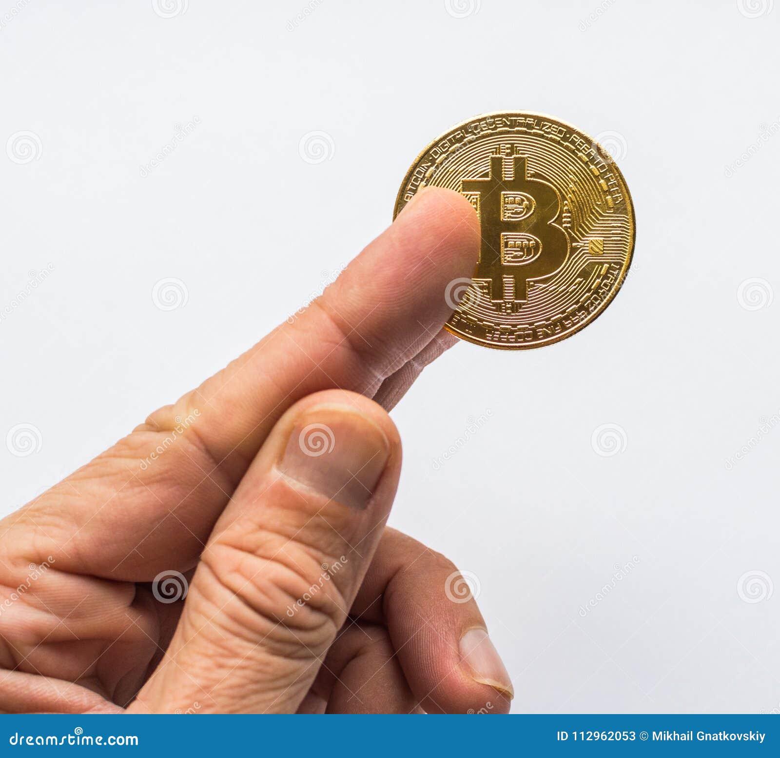 Mão que guarda o dinheiro virtual dourado de Bitcoin