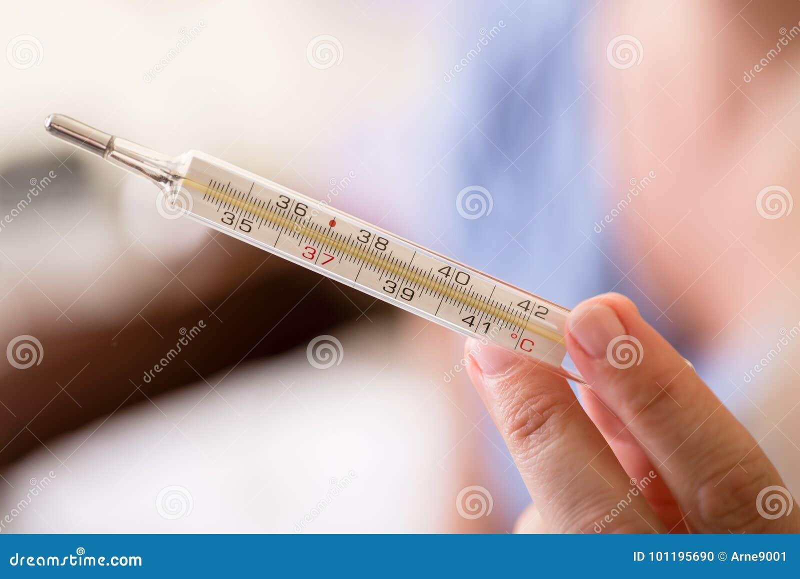 Mão que guarda o termômetro médico análogo