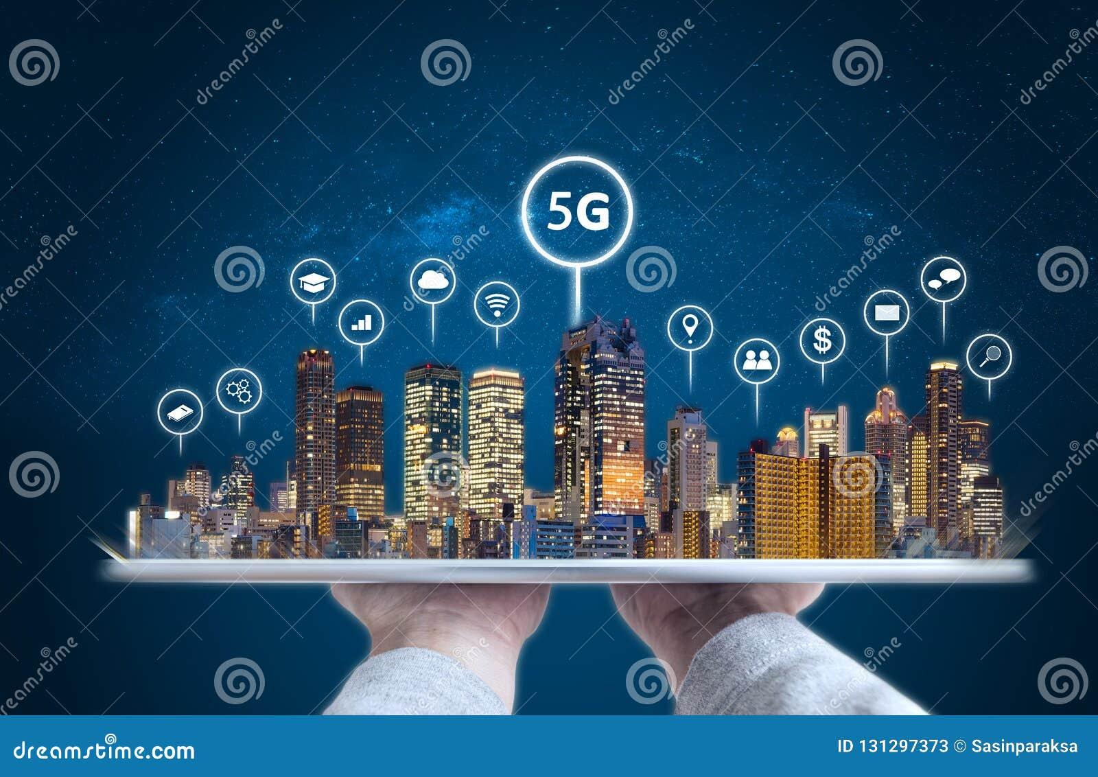 Mão que guarda a tabuleta digital com ícones modernos do holograma e da tecnologia das construções Technolog esperto da cidade, d