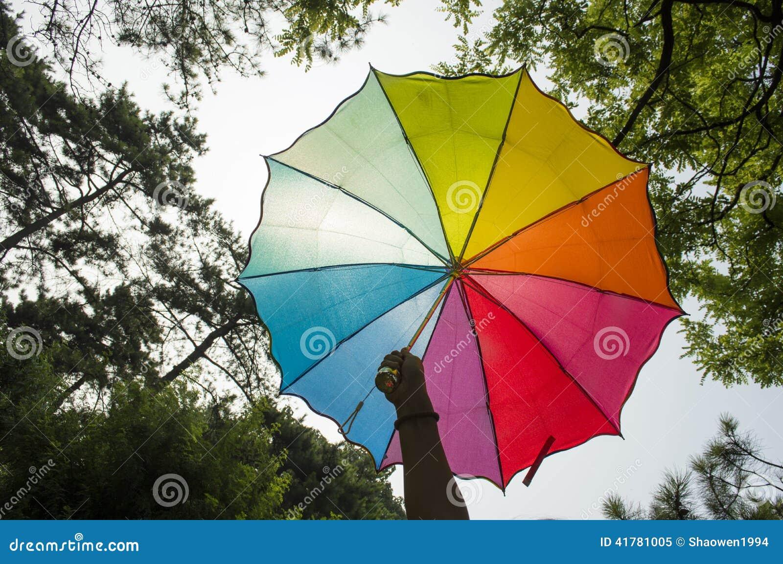 Mão que guarda um guarda-chuva do arco-íris