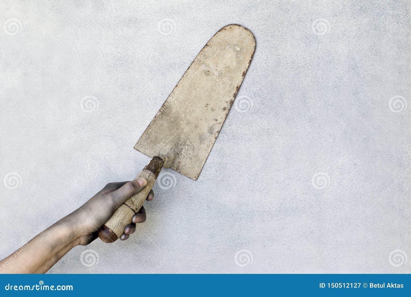 Mão que guarda uma pá de pedreiro do emplastro no fundo cinzento
