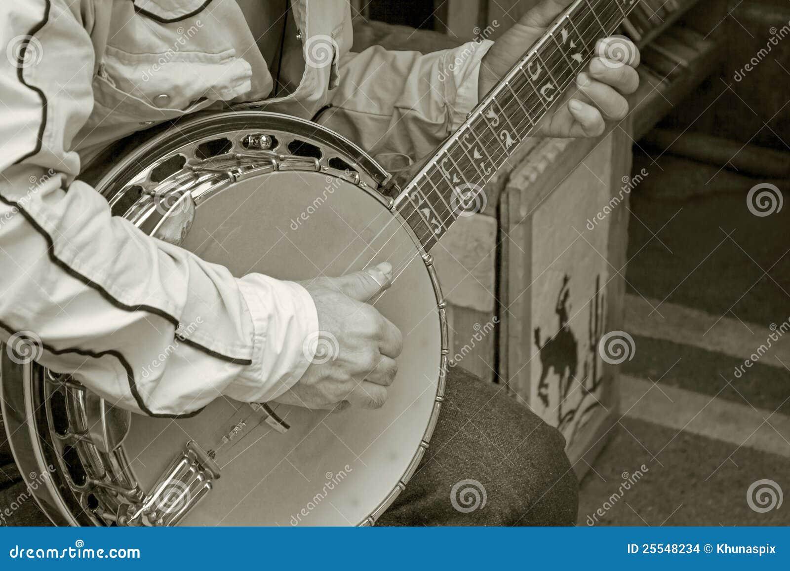 Mão que joga a cor monotone da guitarra do banjo