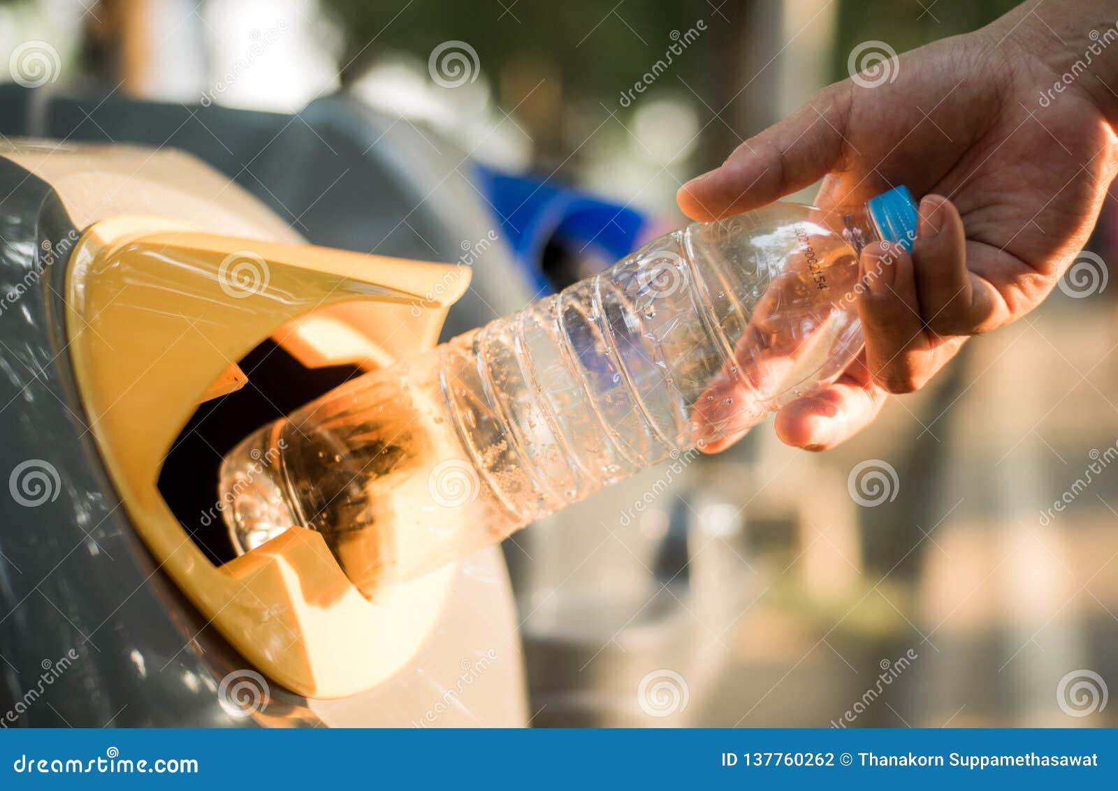 Mão que joga a garrafa plástica no escaninho de reciclagem, aquecimento global