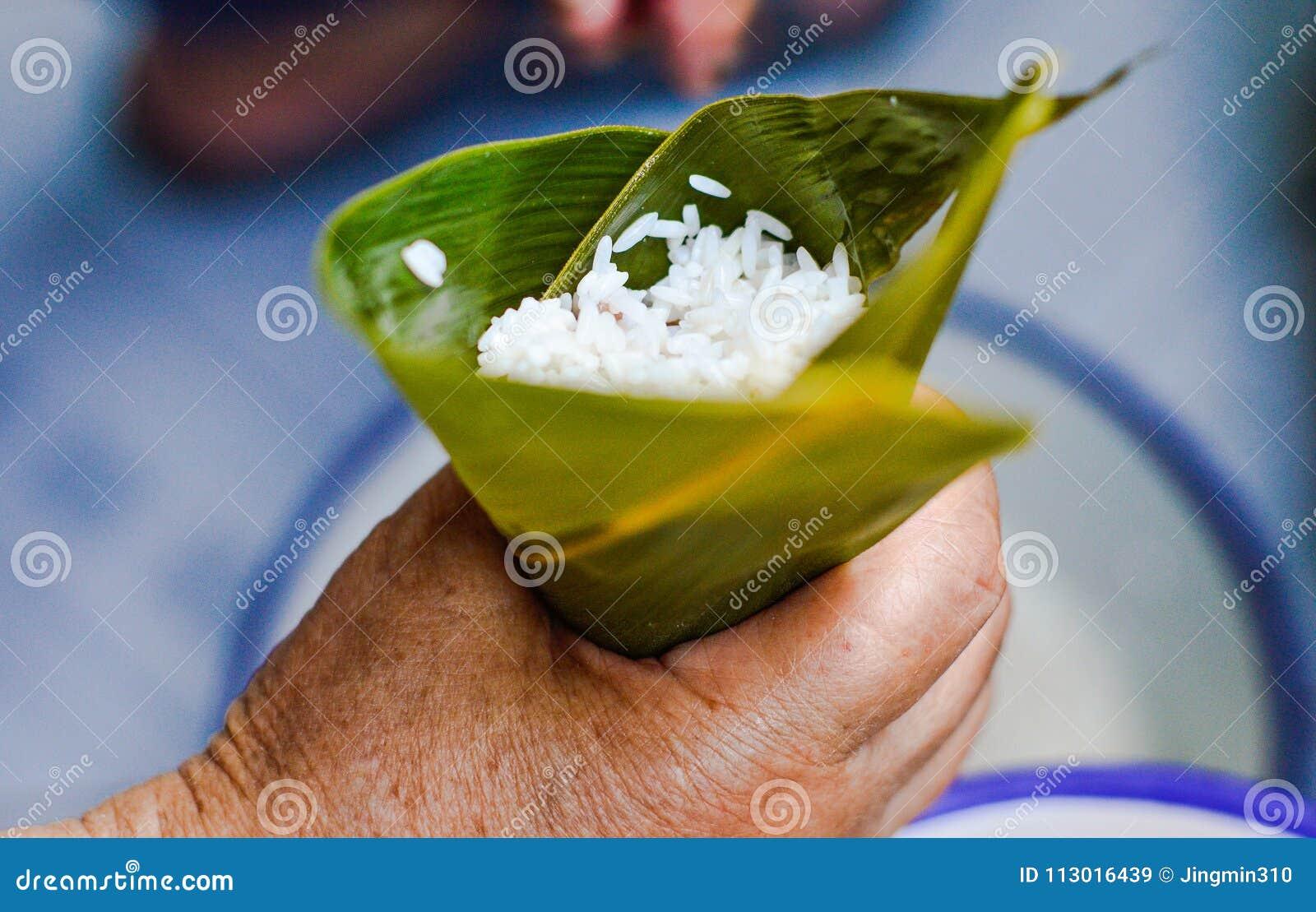Mão que mantém a folha enchida pelo arroz pegajoso para fazer Zongzi