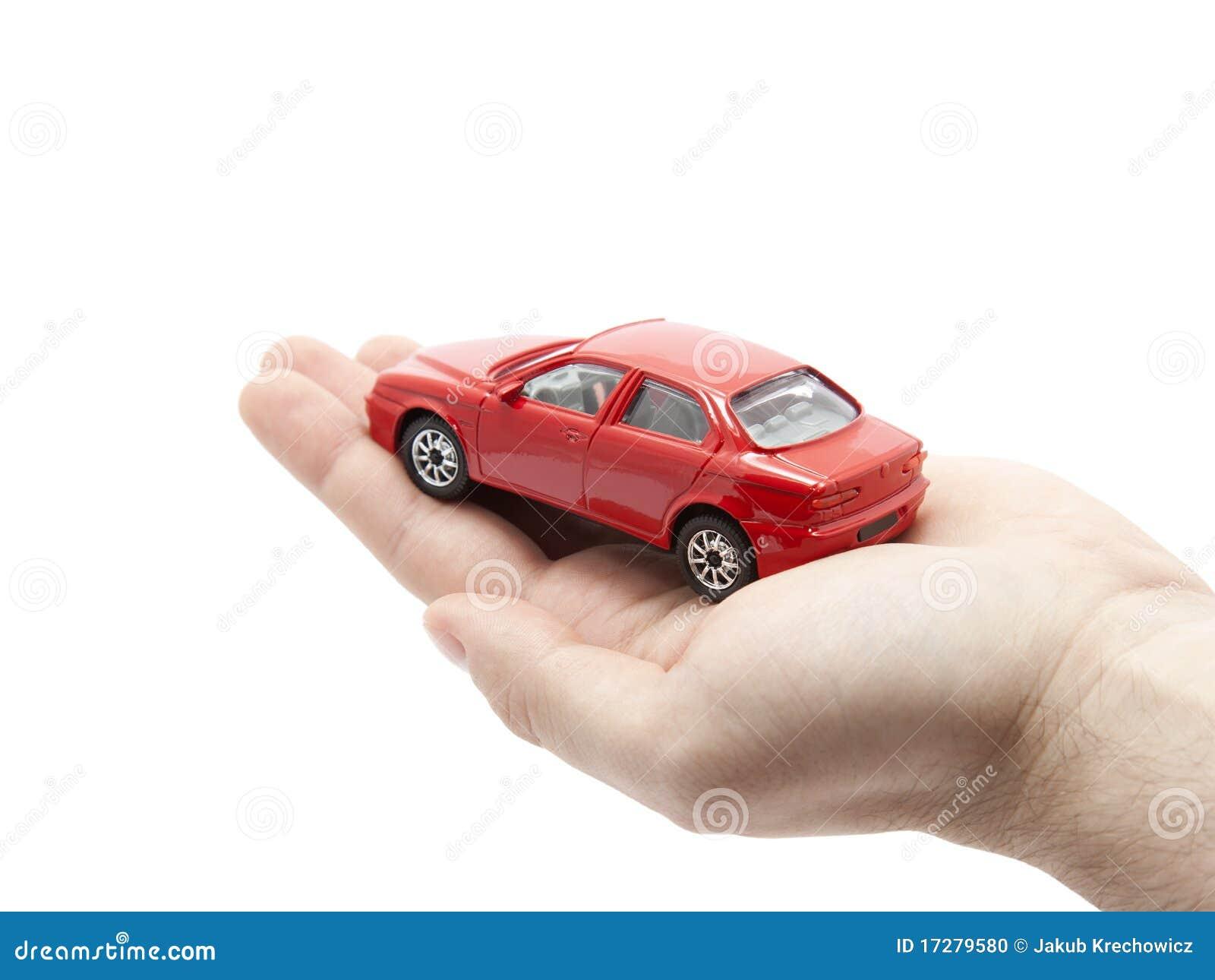 Mão que prende um carro vermelho pequeno